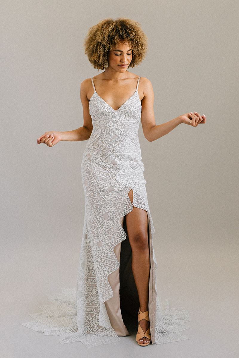 Geometric lace, satin mocha lining, and a thigh-high leg slit come together for an incredibly unique wedding dress