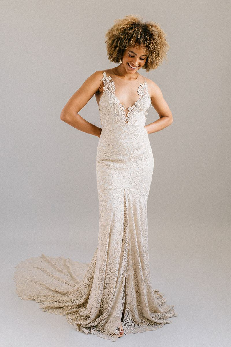 Modern wedding gown with a plunging neckline, long train, and gold fabric