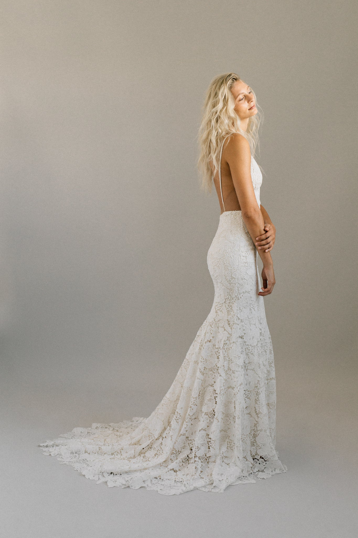 Boho backless wedding dress with bold floral lace, spaghetti straps, and a long train