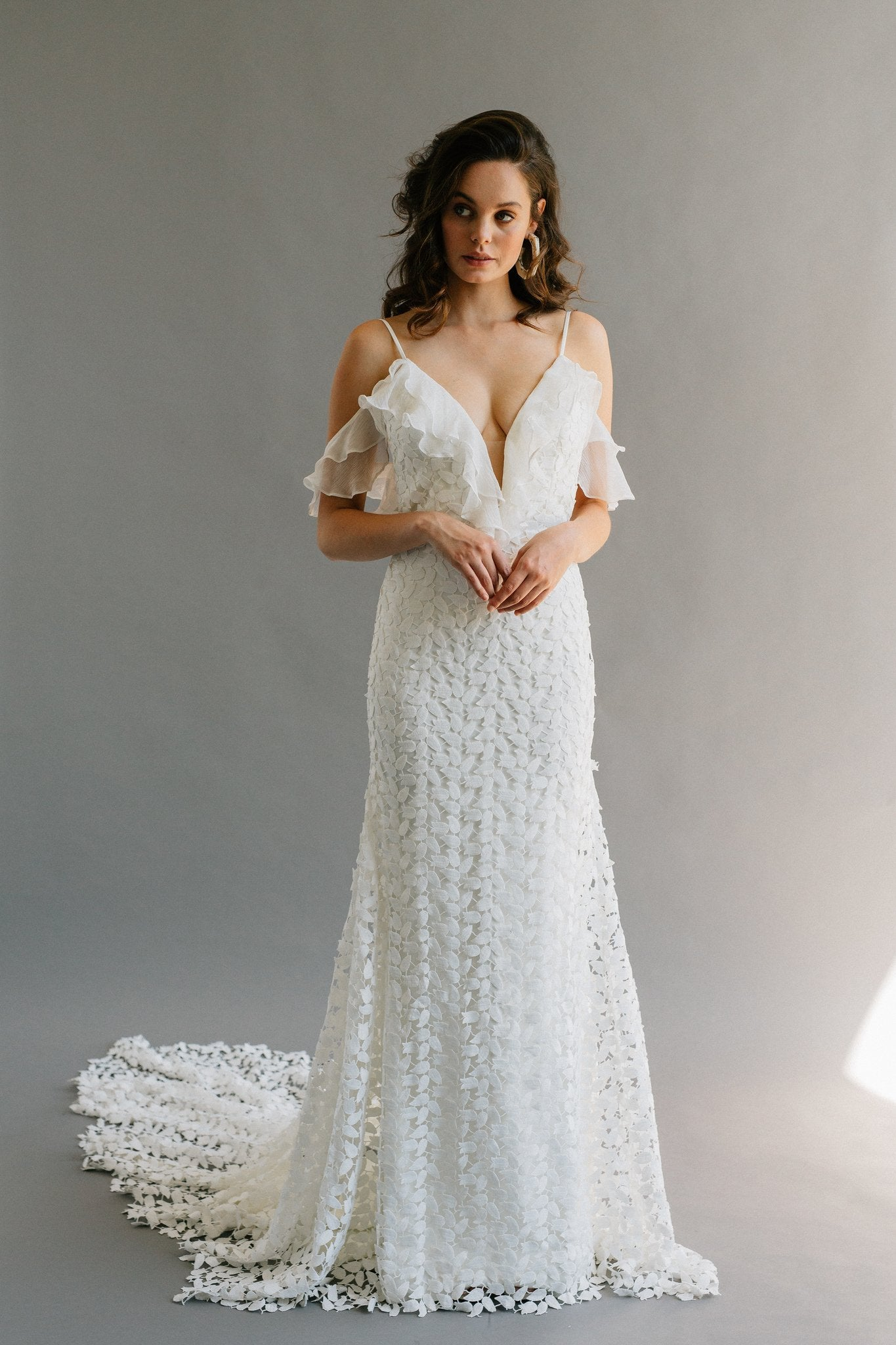 Modern boho wedding dress featuring off the shoulder silk ruffles, a leafy lace, and a long godet train