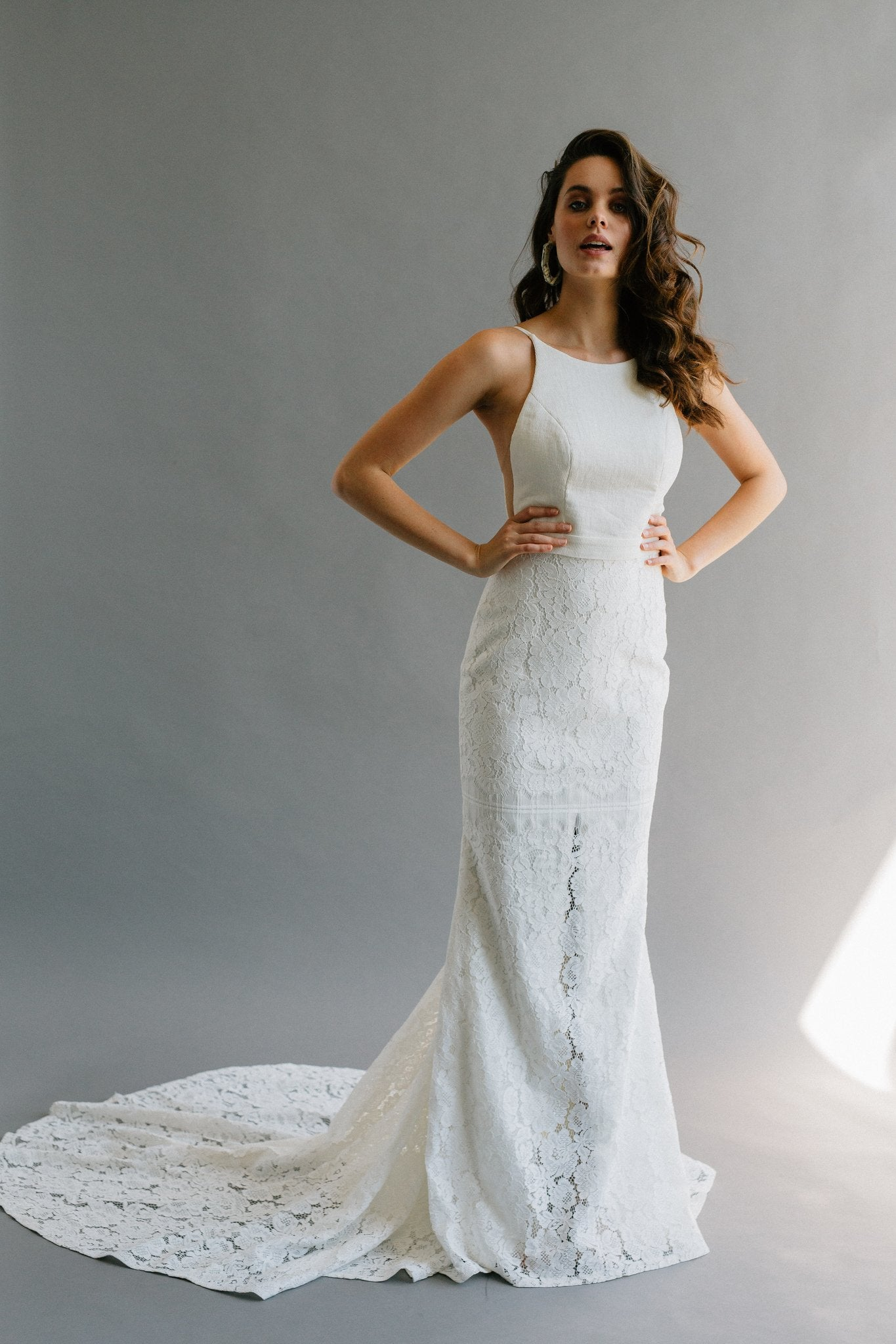 A modern fitted wedding dress with a high neck, low back, and hidden slit in the lace skirt.