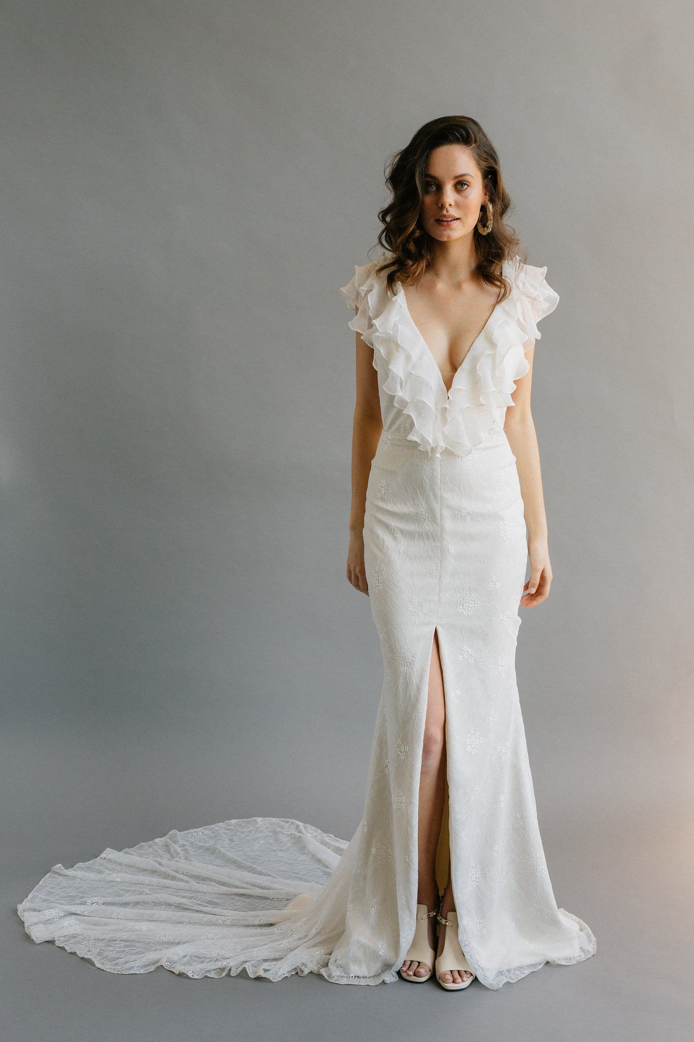 Lightweight mermaid wedding dress with ruffles, a long train, and a slit