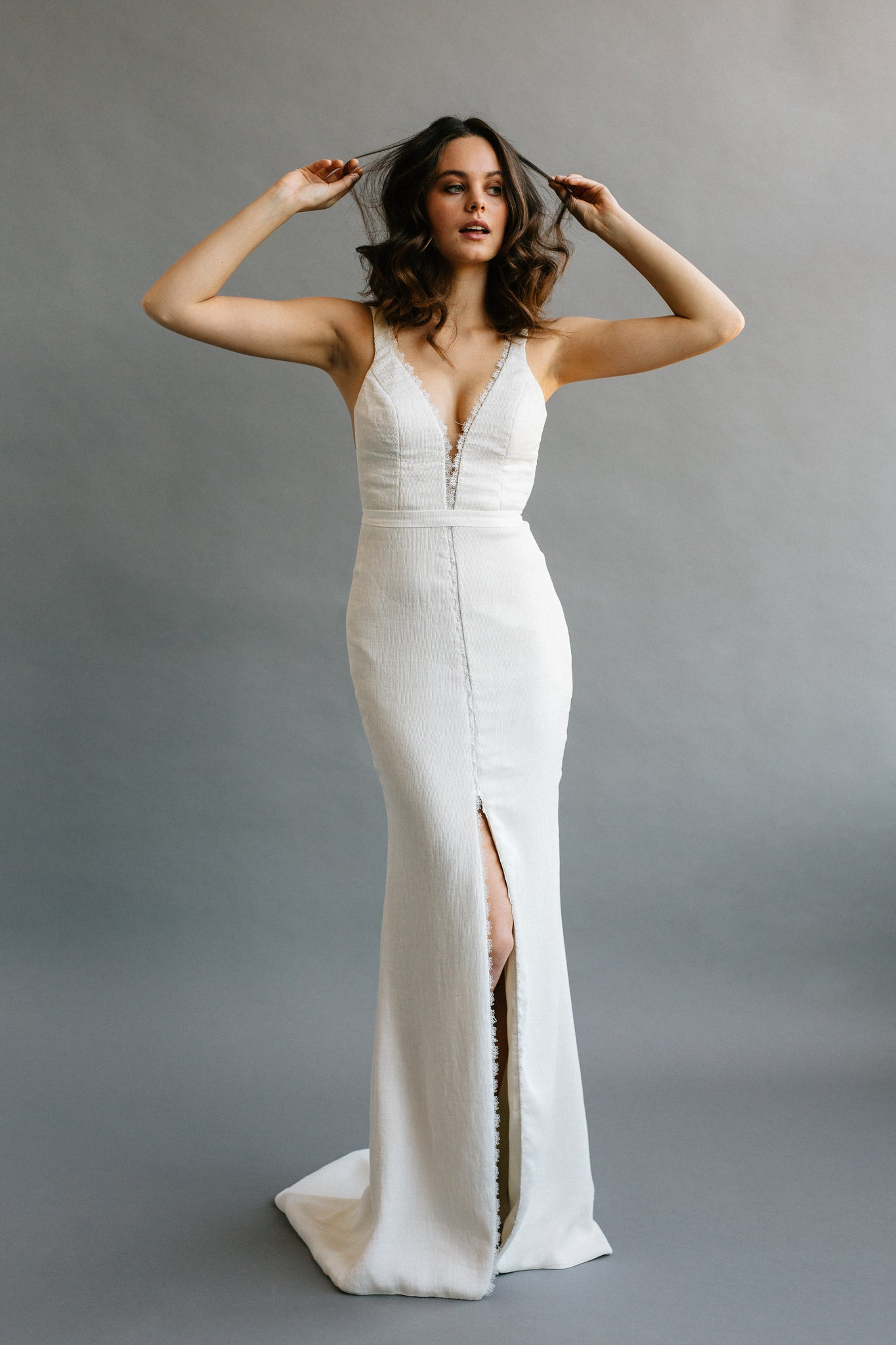 A modern simple wedding gown with a deep v, low back, made ethically by hand with a lightweight ribbed crepe