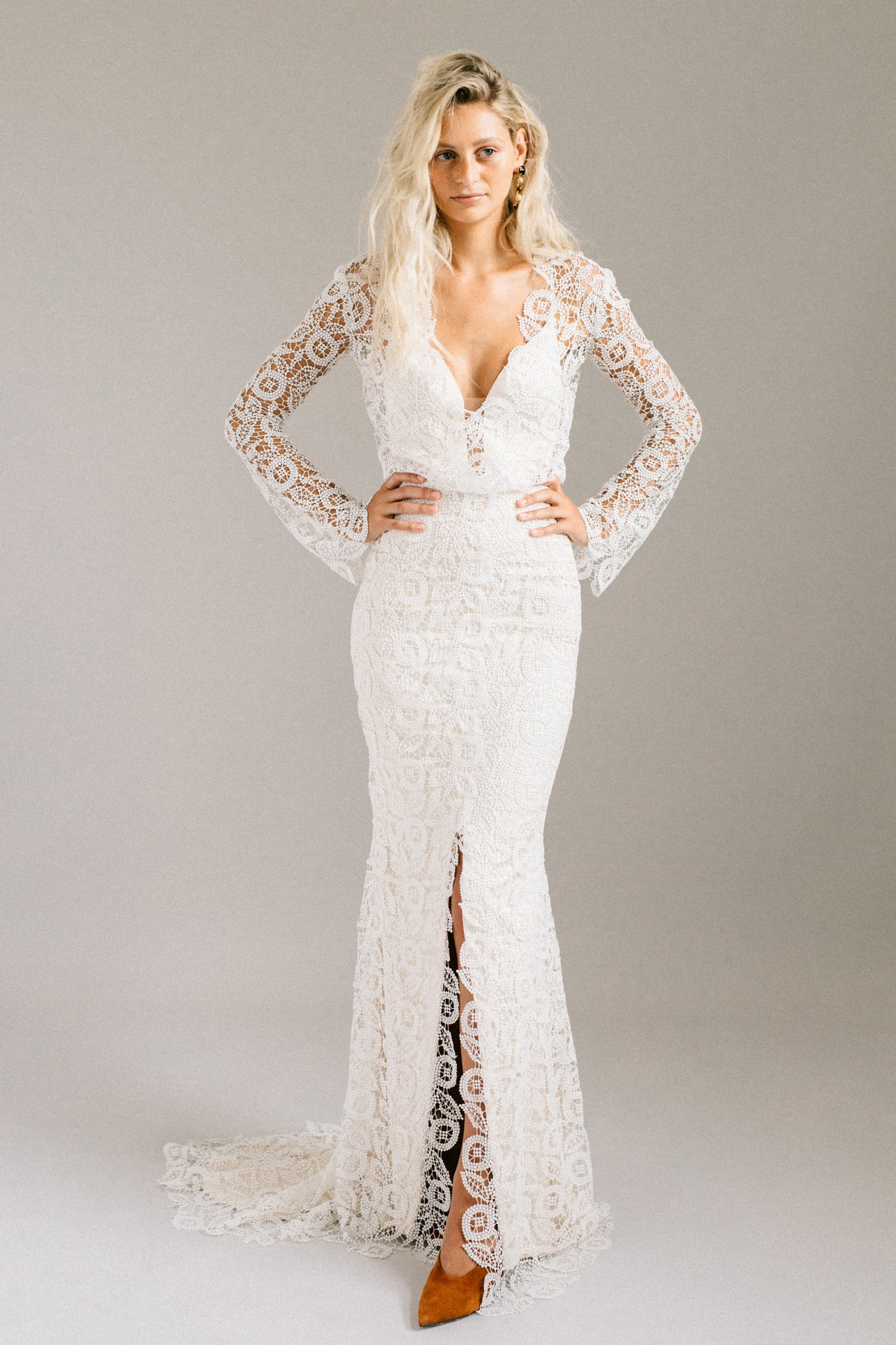 Retro-inspired mermaid wedding dress with bell sleeves, a centre slit, and a short train