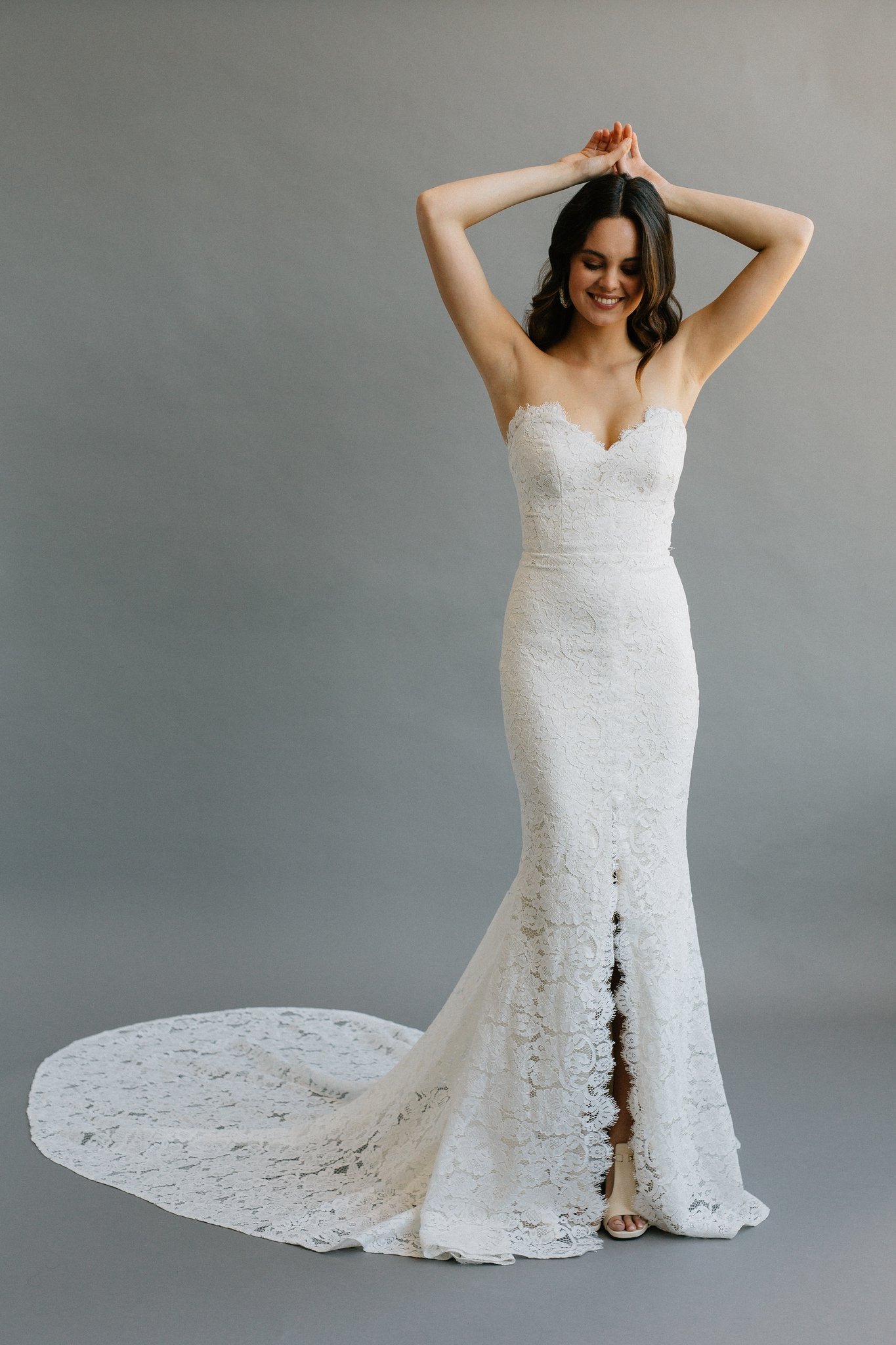 An elegant strapless sweetheart fitted wedding dress with a centre slit, long train, and a pearl button-up back