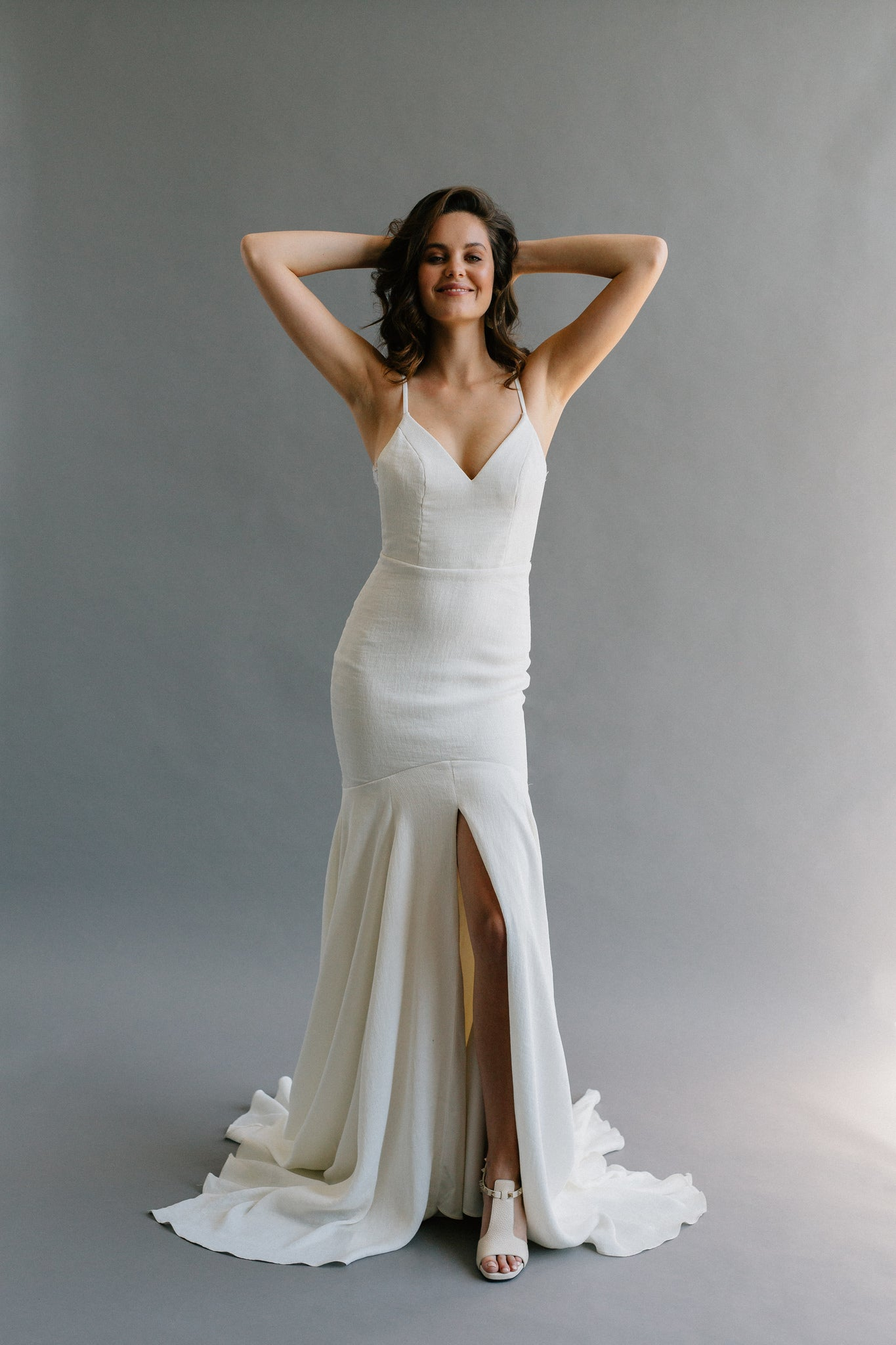 Non-traditional wedding dress made in a textured crepe with a centre slit, lace panels, and a four-point train