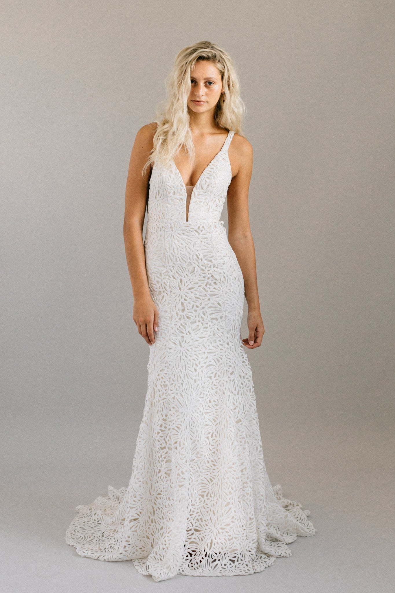 Unique lace mermaid wedding dress with a deep v front and back and a sweeping train