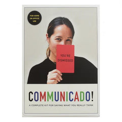 "Front of the box for a game called Communicado, with a girl holding up a card saying ""you're dismissed!"""
