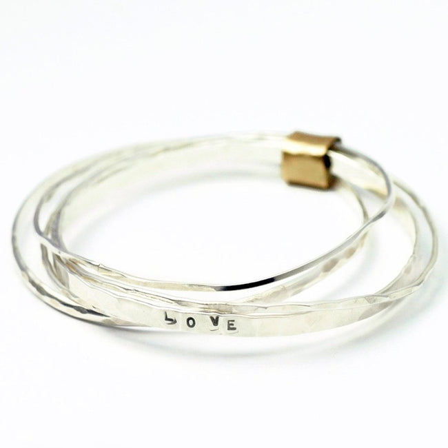 stacking bangles wrapped in 14 karat yellow gold