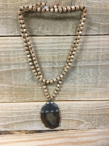 Iridescent necklace with a light brown rock drop.