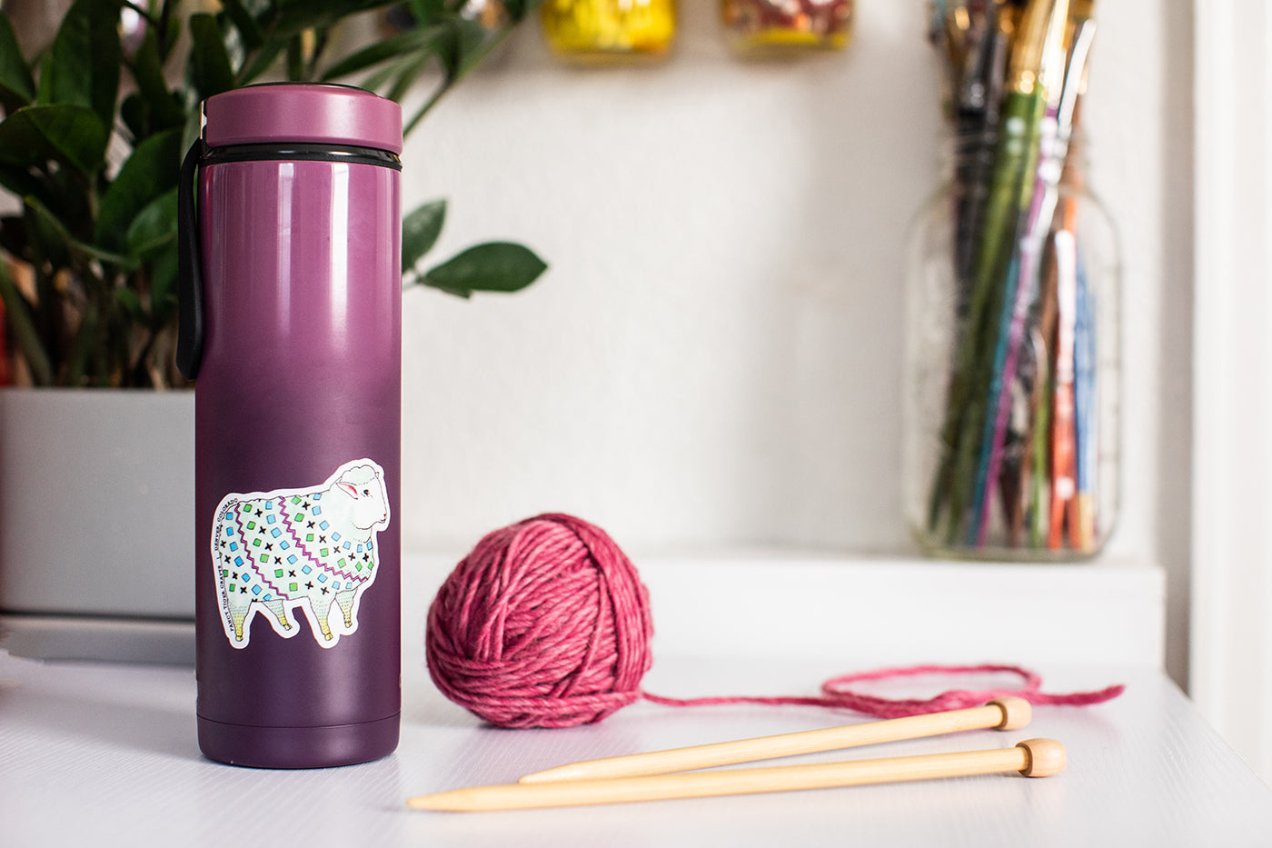 This is an image of a purple water bottle with a sheep sticker on the side of it and a ball of yarn and knitting needles sitting beside it