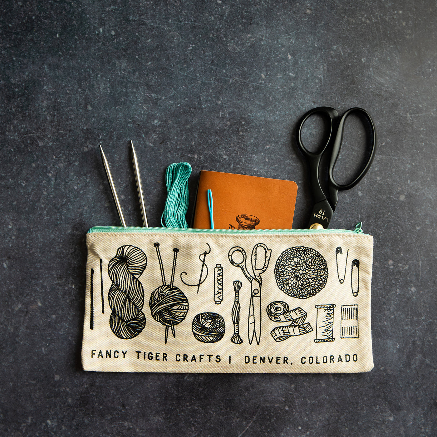 This is an image of a zipper pouch against a granite counter top with scissors, a notebook and other sewing tools sticking out of the top
