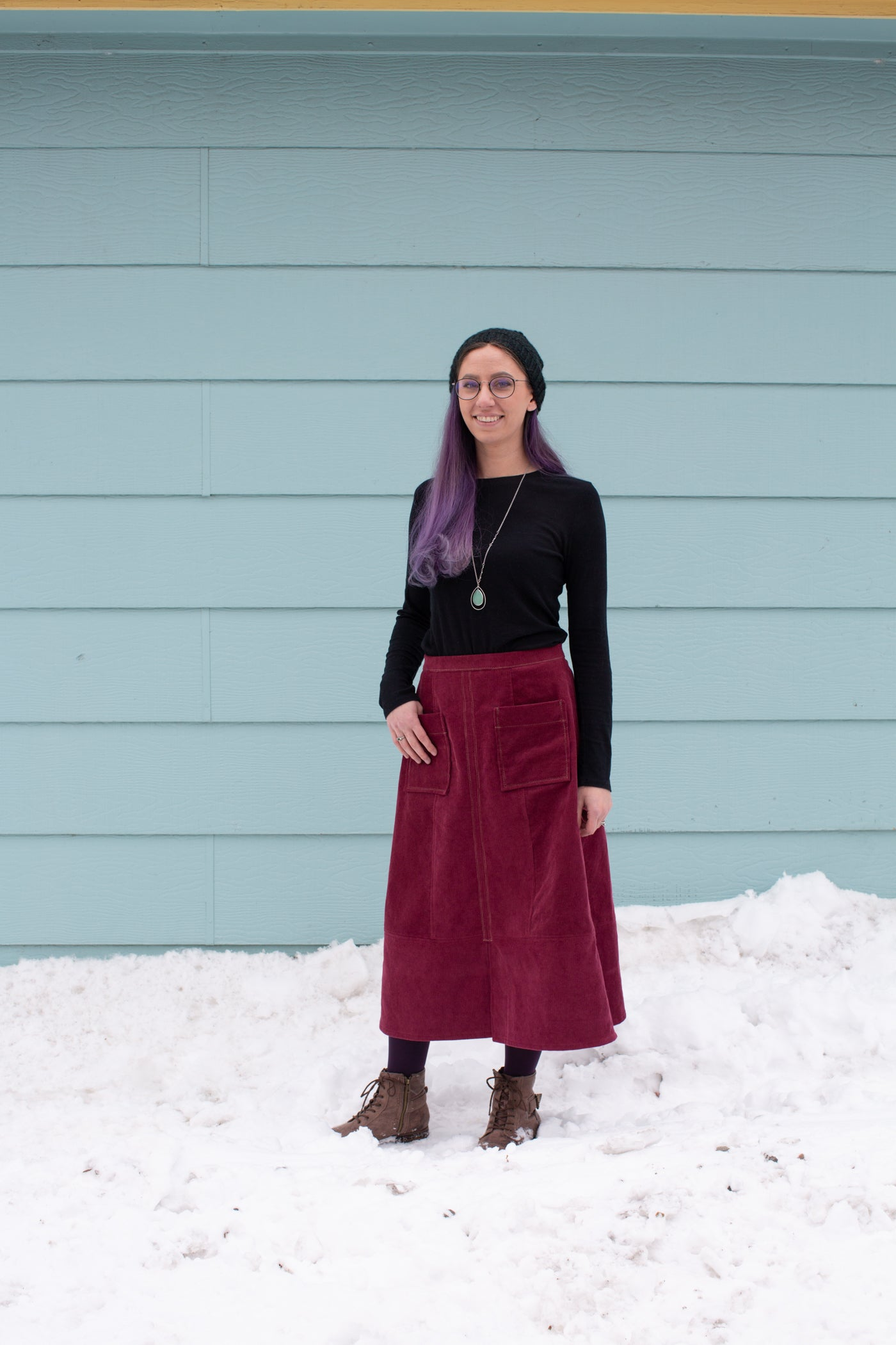 Aly standing in snow against a sea blue wall wearing a Reed Skirt in merlot corduroy and black long sleeve top.