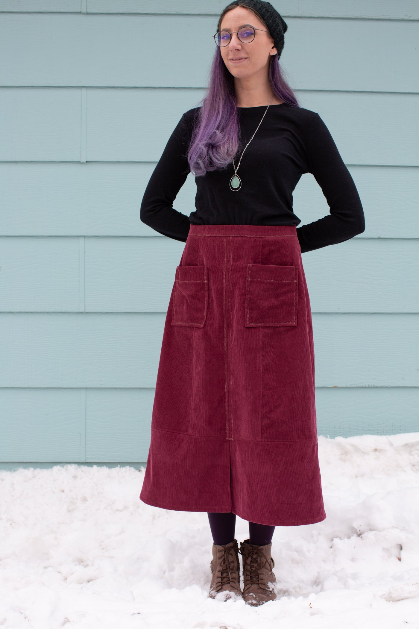 Aly standing in snow against a sea blue wall with her arms behind her back.  Aly is wearing a Robert Kaufman Corduroy skirt in merlot with a black long sleeve top.
