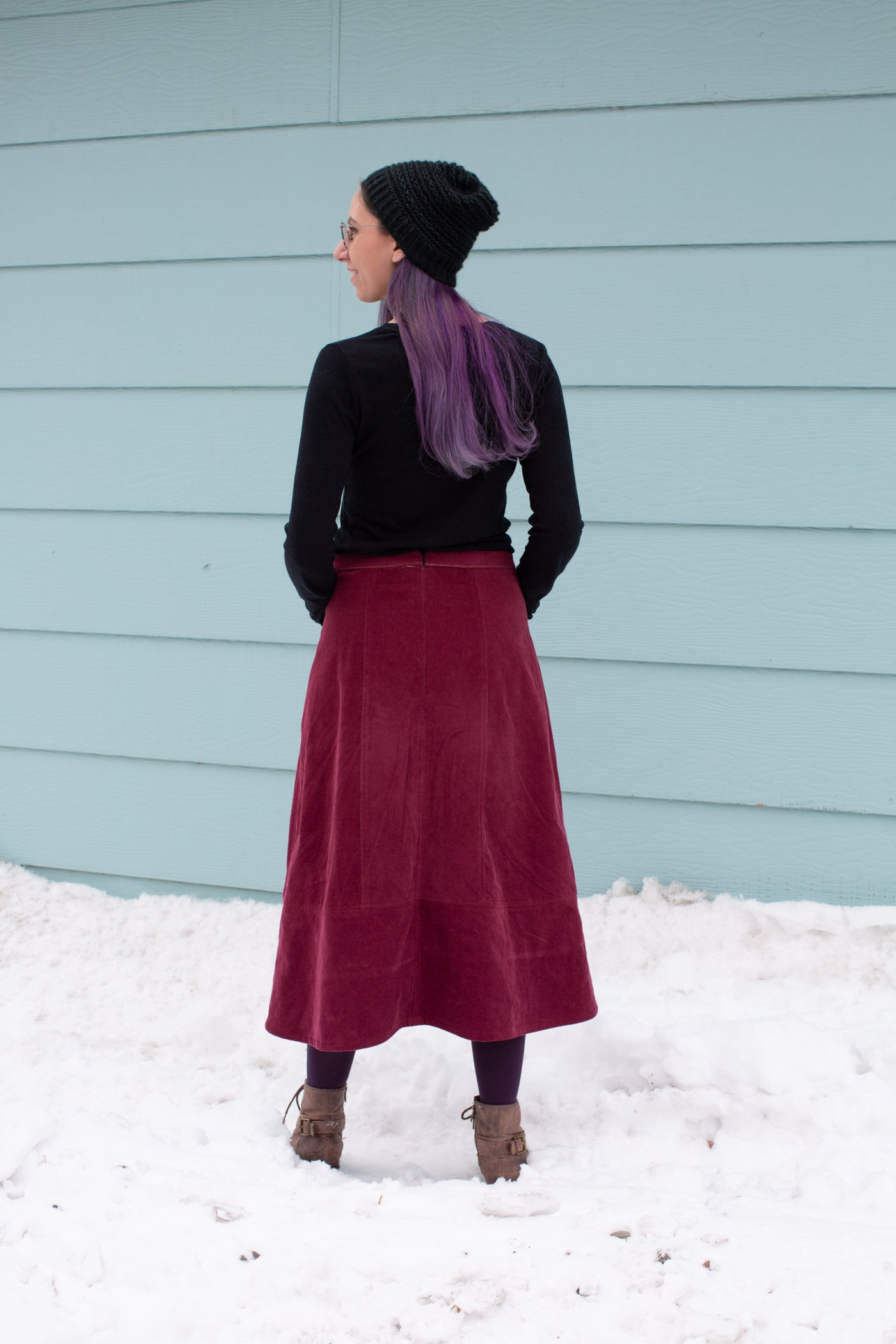 Aly is wearing a Robert Kaufman Corduroy skirt in merlot with a black long sleeve top.  Aly is standing in snow against a sea blue wall facing away from the camera, showing the back of the pattern.