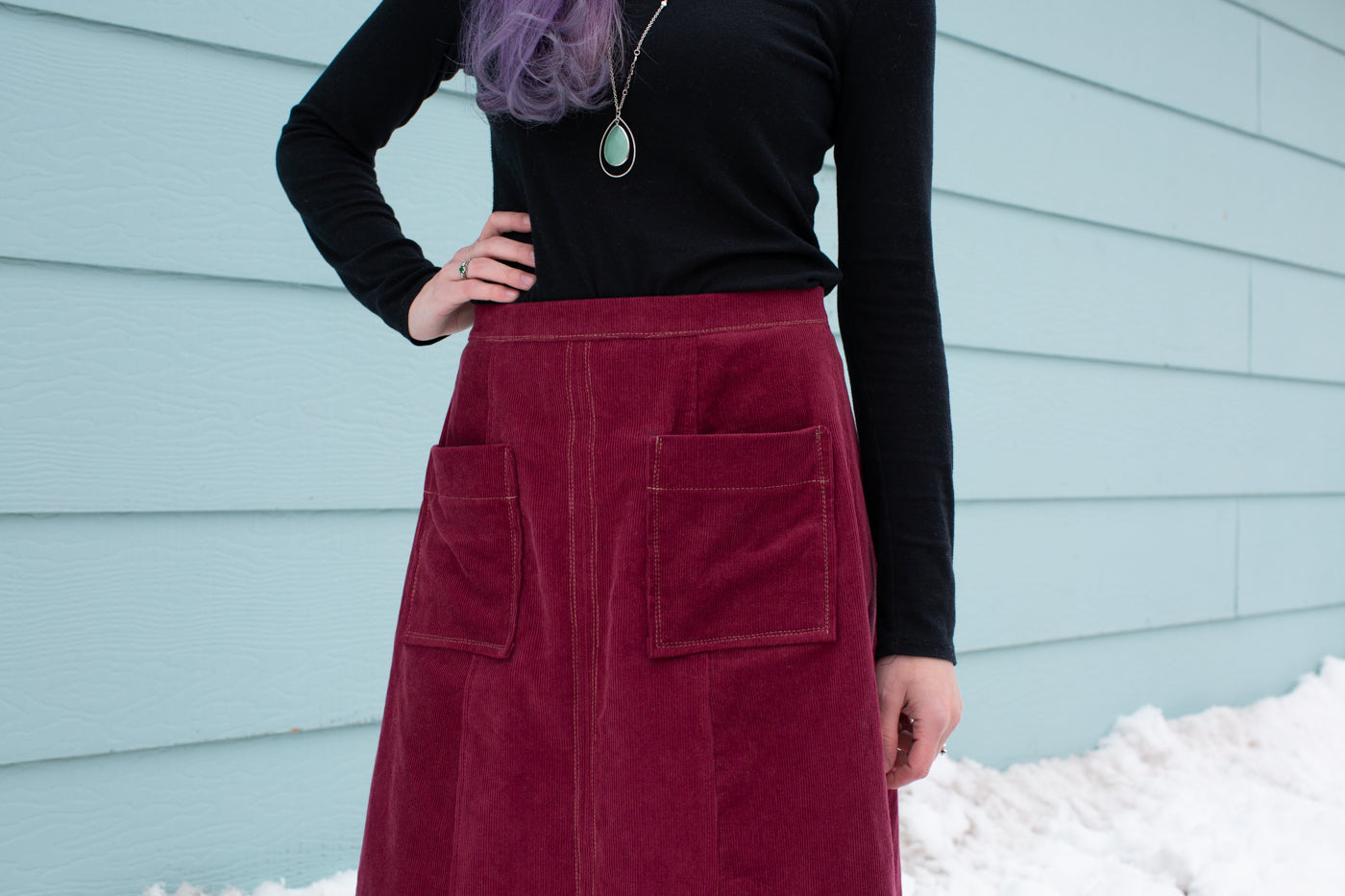 Aly standing in snow against a sea blue wall wearing a Reed Skirt in merlot corduroy and black long sleeve top. Close-up photograph of the the pockets with white stitching on the skirt..