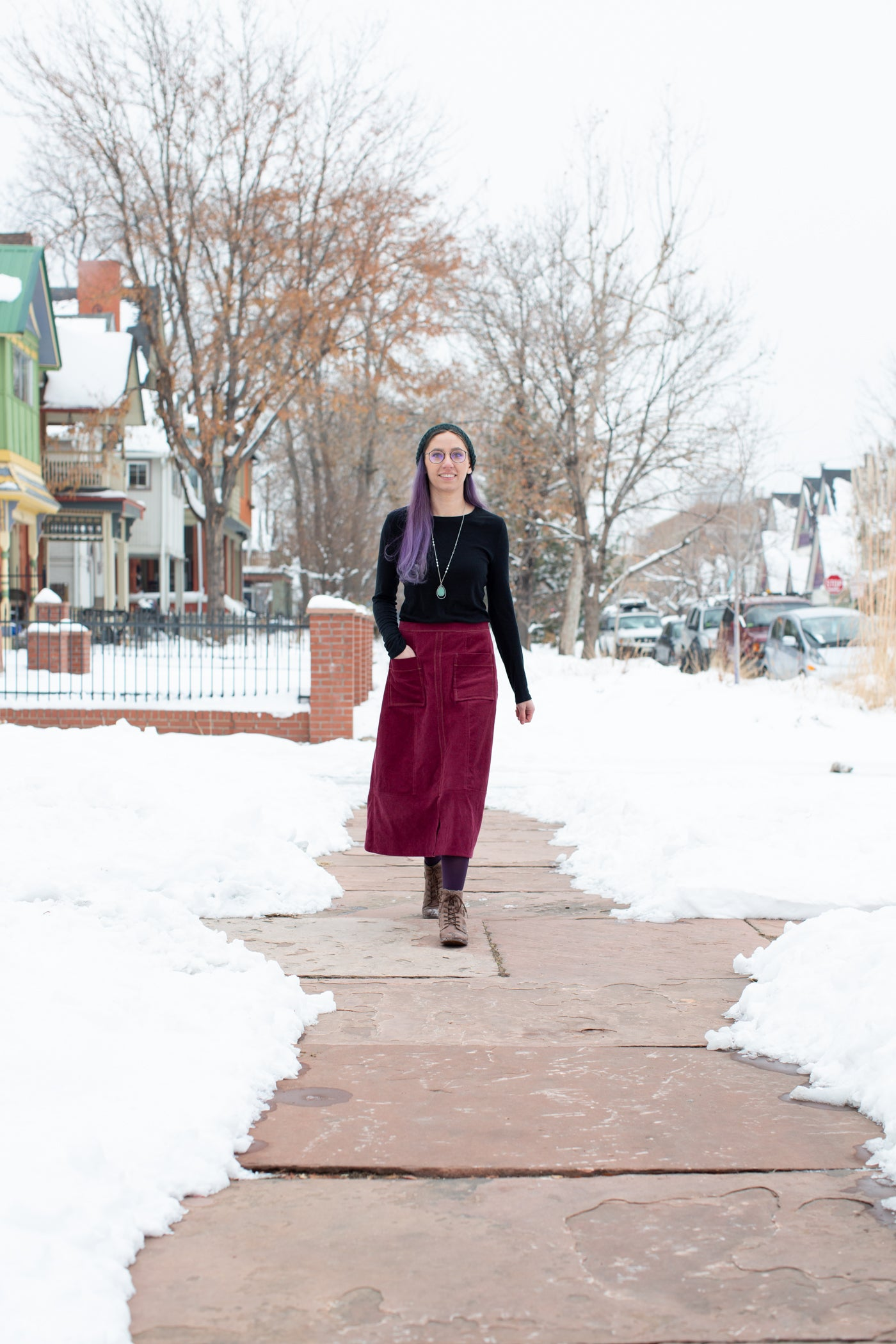 Aly is walking down a city sidewalk, with snow on both sides of the sidewalk.  Aly is wearing a Robert Kaufman Corduroy skirt in merlot with a black long sleeve top.