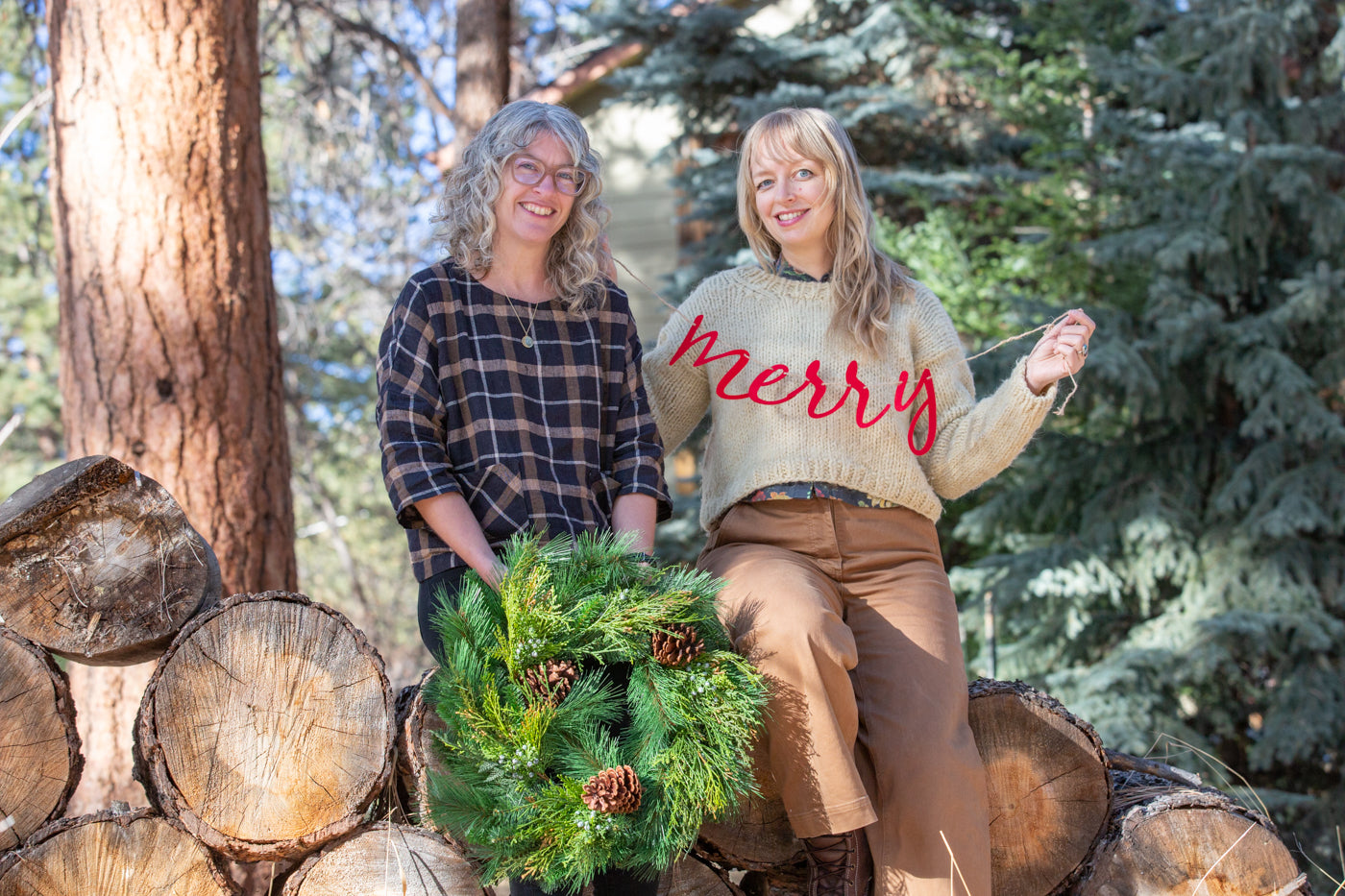 Jaime and Amber sitting on a wood pile, smiling.  Jaime is holding a Christmas wreath and Amber is holding a red felt sign that says Merry.  The background is Colorado pine trees.