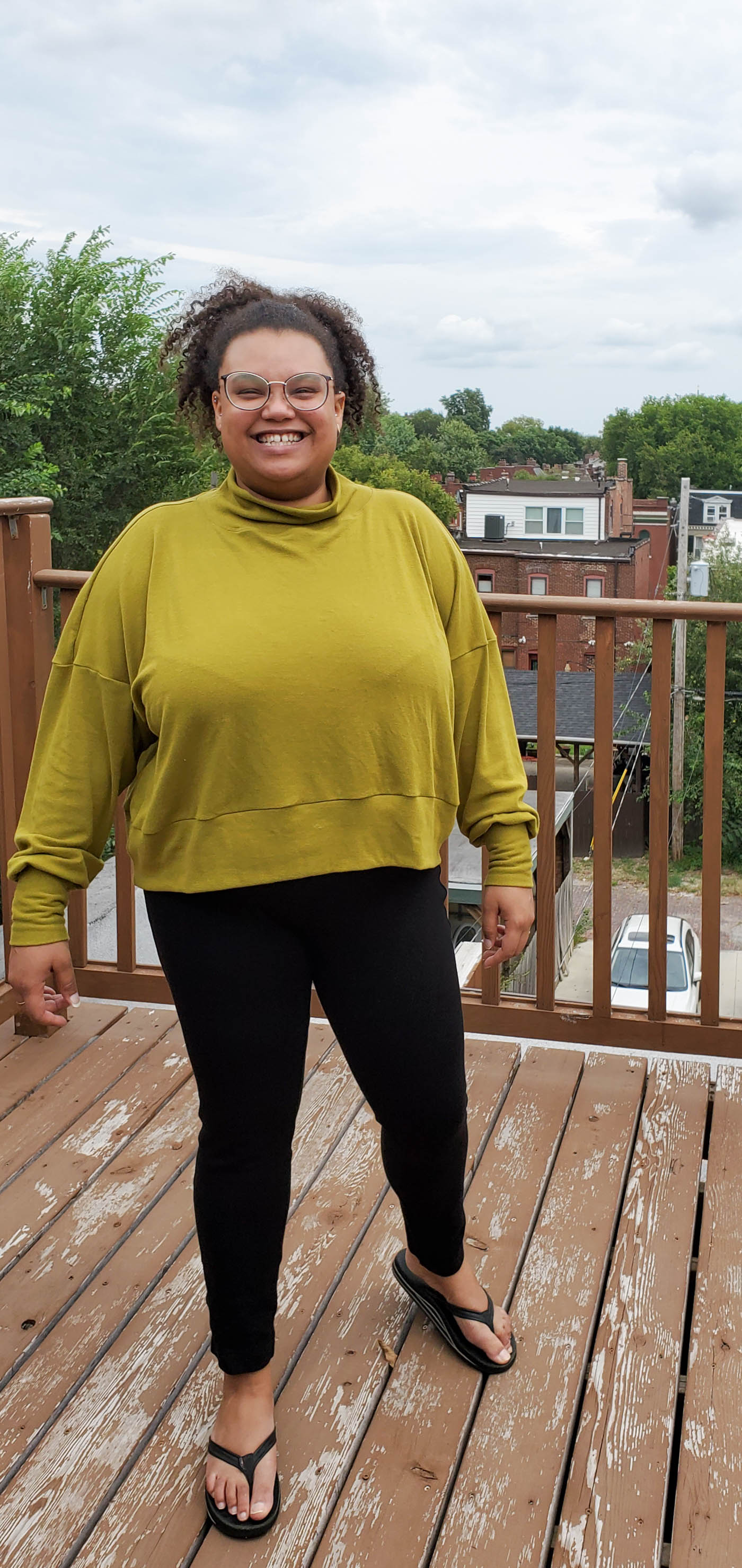 Women wearing a Hosta Tee long sleeve in Bamboo Cotton Stretch Rib in Chartreuse and black jeans.  Women is standing on an outdoor patio in the city with cloudy blue skies and looking straight on to the camera and smiling.