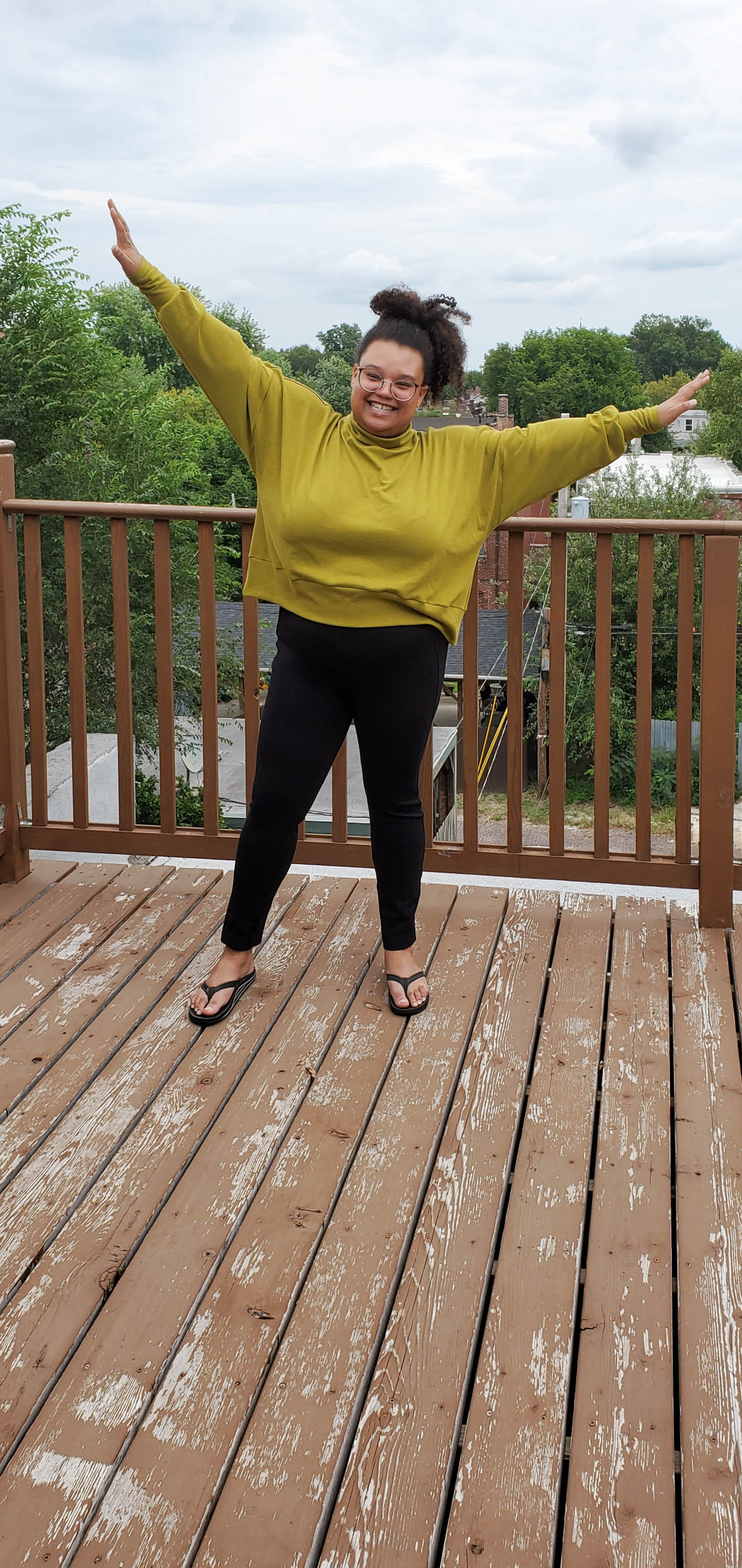 Women wearing a Hosta Tee long sleeve in Bamboo Cotton Stretch Rib in Chartreuse and black jeans..  Women is standing on an outdoor patio in the city with cloudy blue skies and her arms raised up in a V.