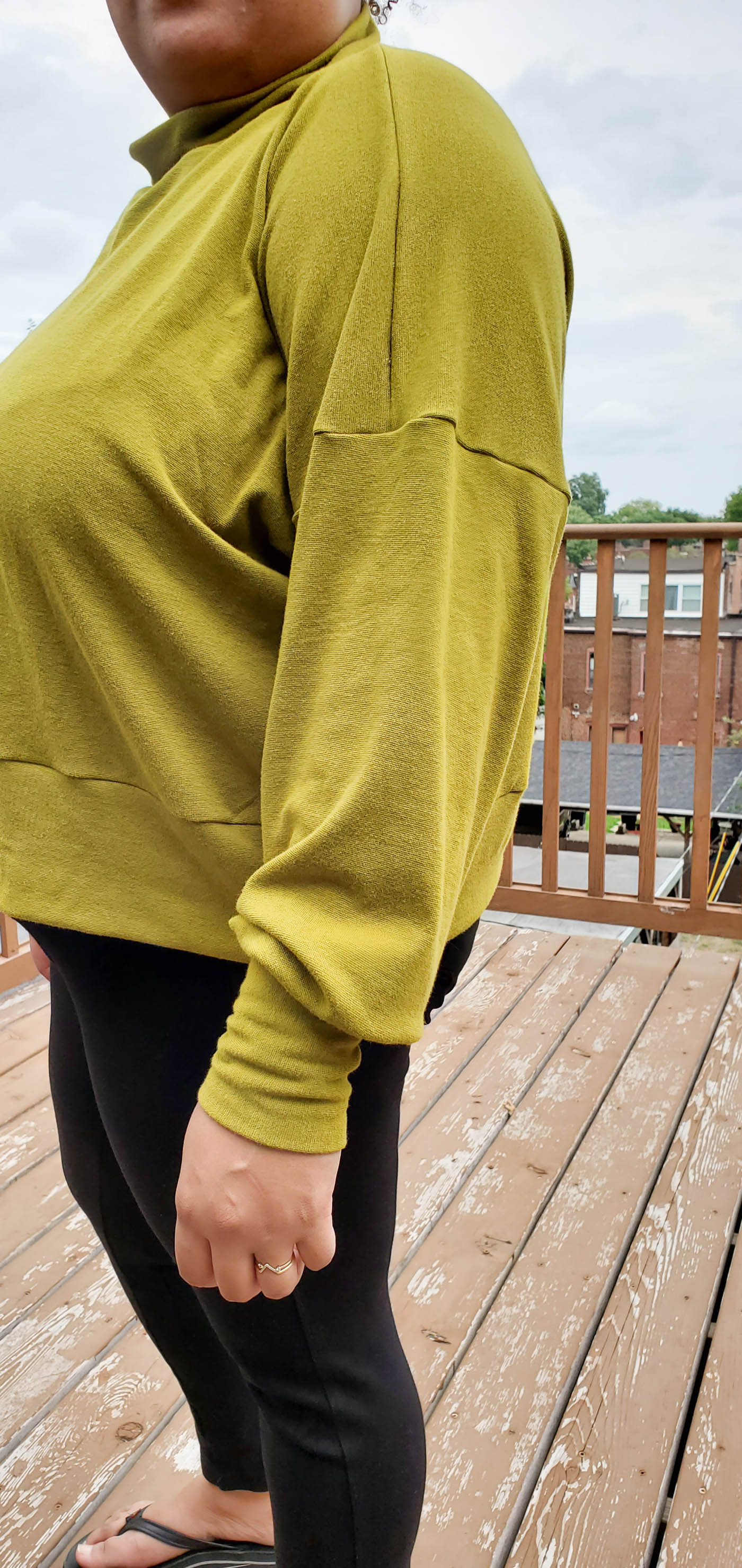Women wearing a Hosta Tee long sleeve in Bamboo Cotton Stretch Rib in Chartreuse and black jeans, standing sideways to the camera.  Detail photograph of the shoulder and sleeve of the shirt.