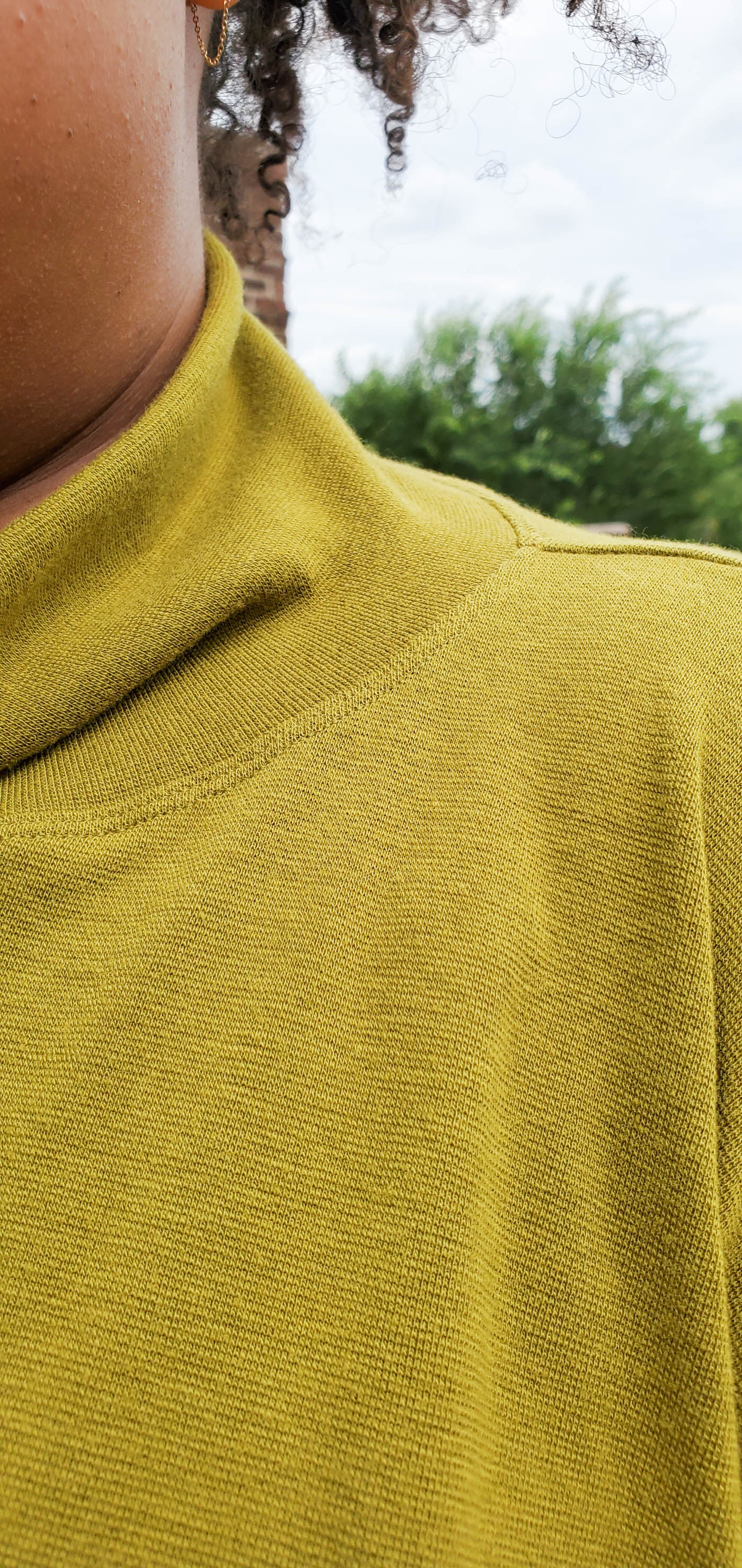 Women wearing a Hosta Tee long sleeve in Bamboo Cotton Stretch Rib in Chartreuse.  Detail photograph of the neckline to show how well the thread matches the fabric.