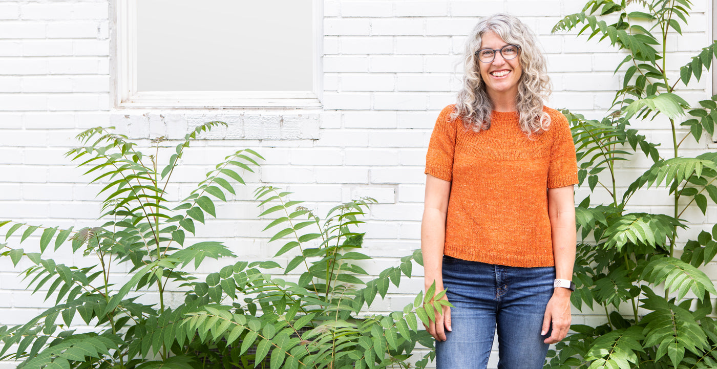 This is a photo of a woman wearing an orange short sleeved sweater in front of a brick wall and greenery