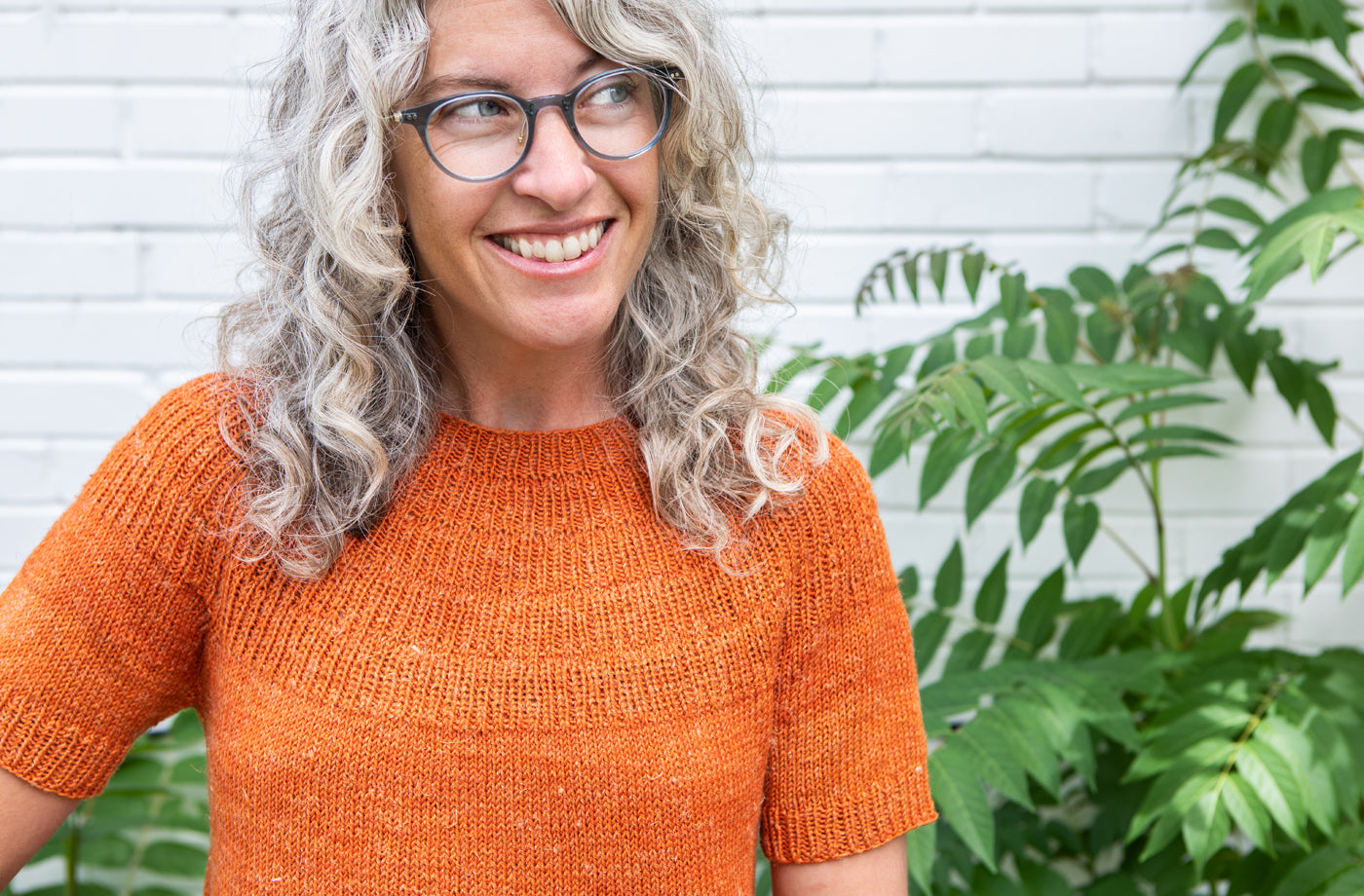 This is an image of a woman wearing an orange short sleeve shirt  standing in front of some greenery and a white brick wall.