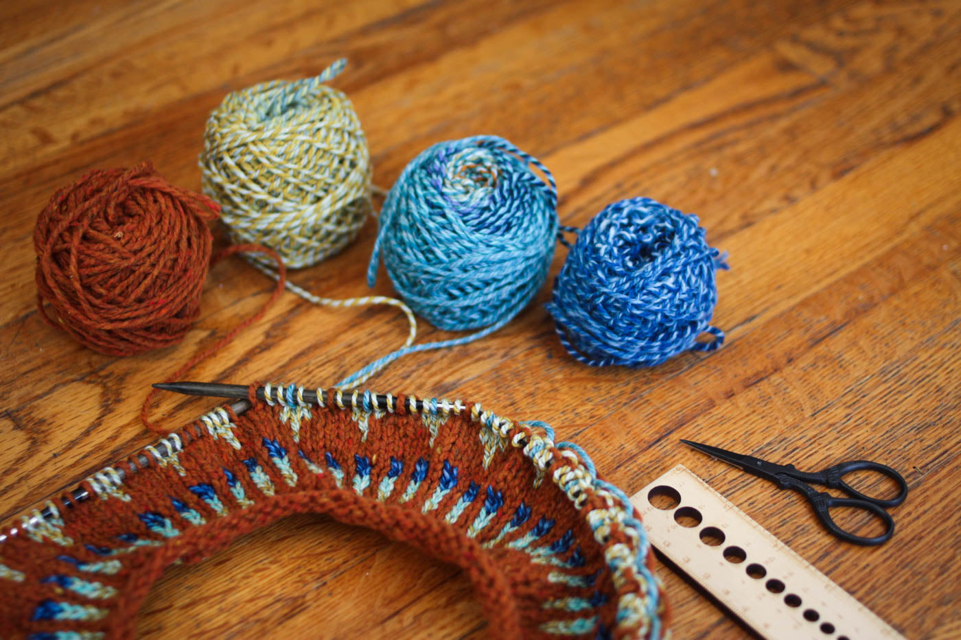 Lay flat image of a sweater being knitted in the round. Above it 4 balls of yarn, left to right: embers red, sea green, light blue and dark blue. To the right of that black scissors and a wooden knitting tool