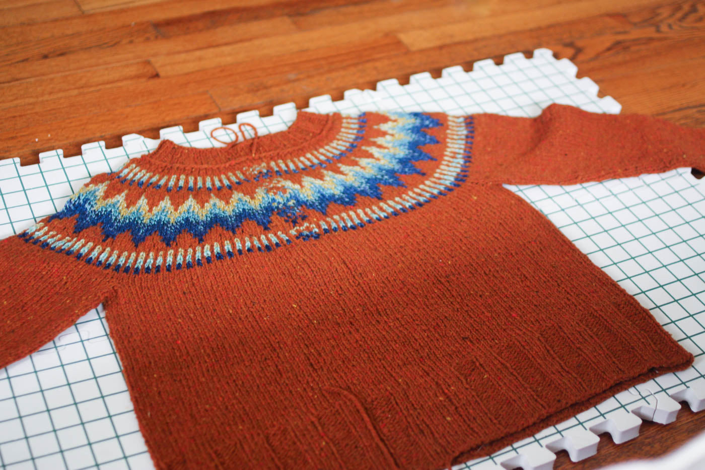 Lay flat photograph of sweater being blocked. Sweater is an embers orange with the top having an ombre in a diamond pattern of blues, green and yellow.