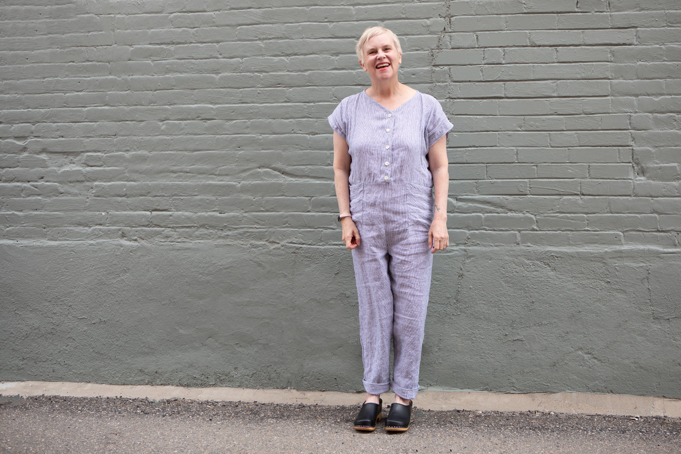 Christina stands outside in front of a sage-green brick wall, her hands at her sides, laughing. She wears a sewn linen jumpsuit, with a v-neck, button front, and short sleeves.