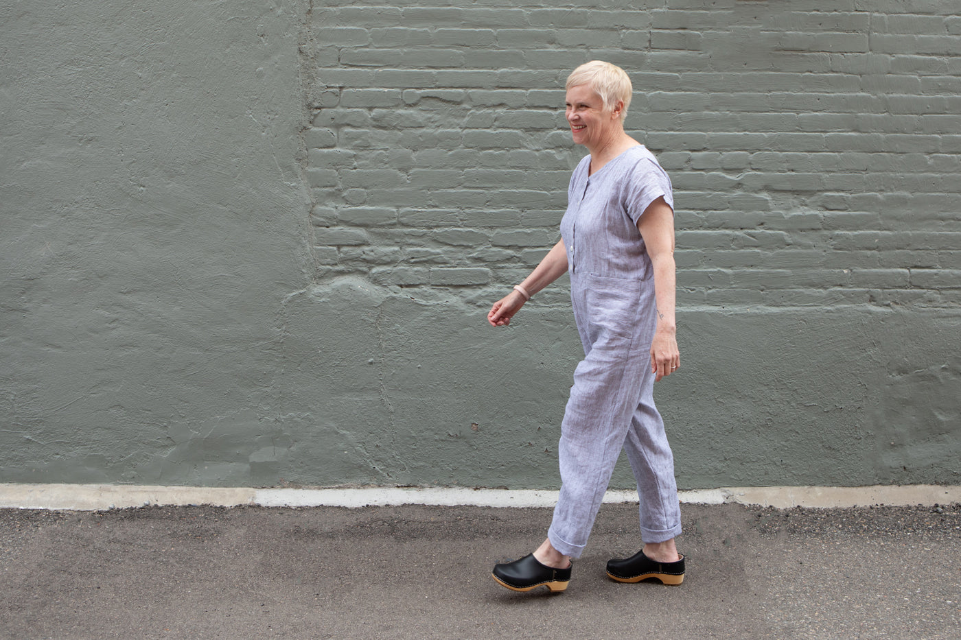 Christina smiles, walking down the sidewalk wearing her hand-made linen jumpsuit from Sonya Philip's The Act of Sewing book.