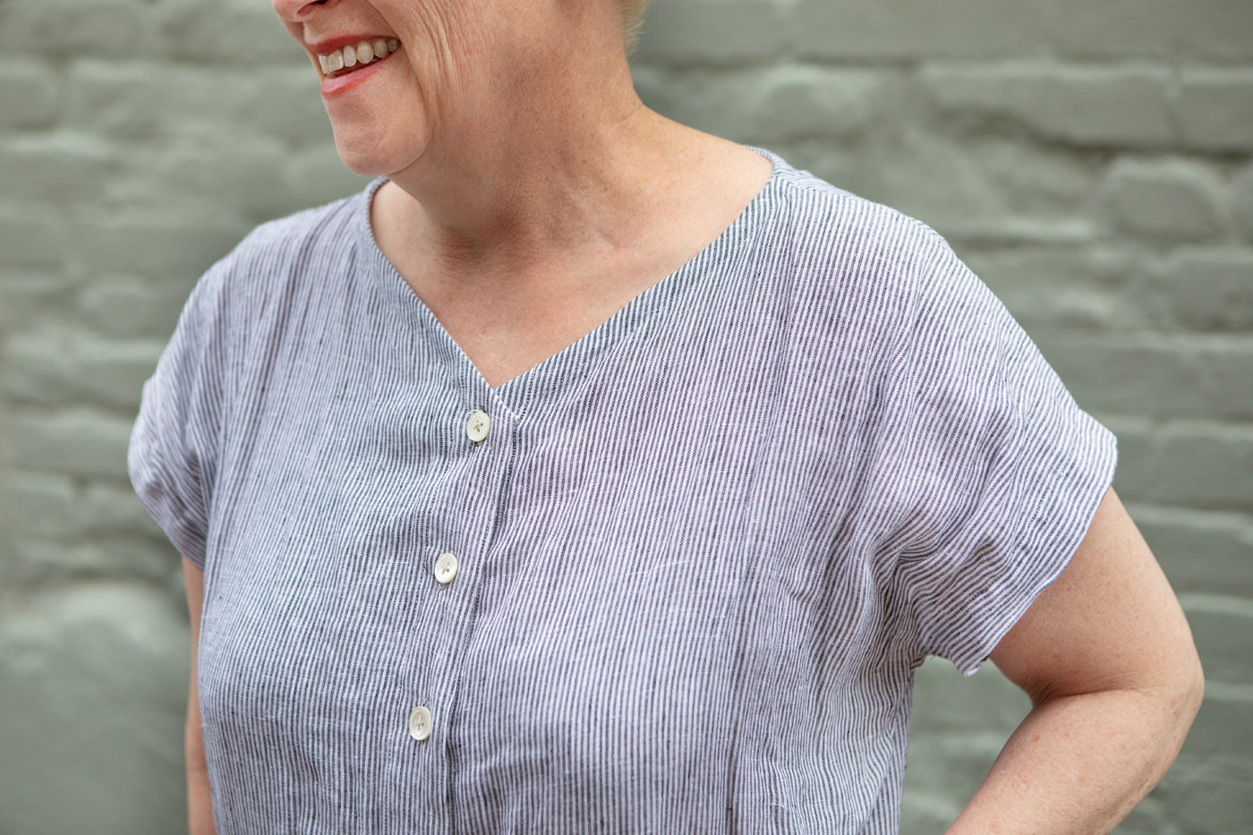 A detail shot of the neckline of Christina's jumpsuit, in a white and grey narrow-striped linen. The front buttons with white mother-of-pearl buttons.