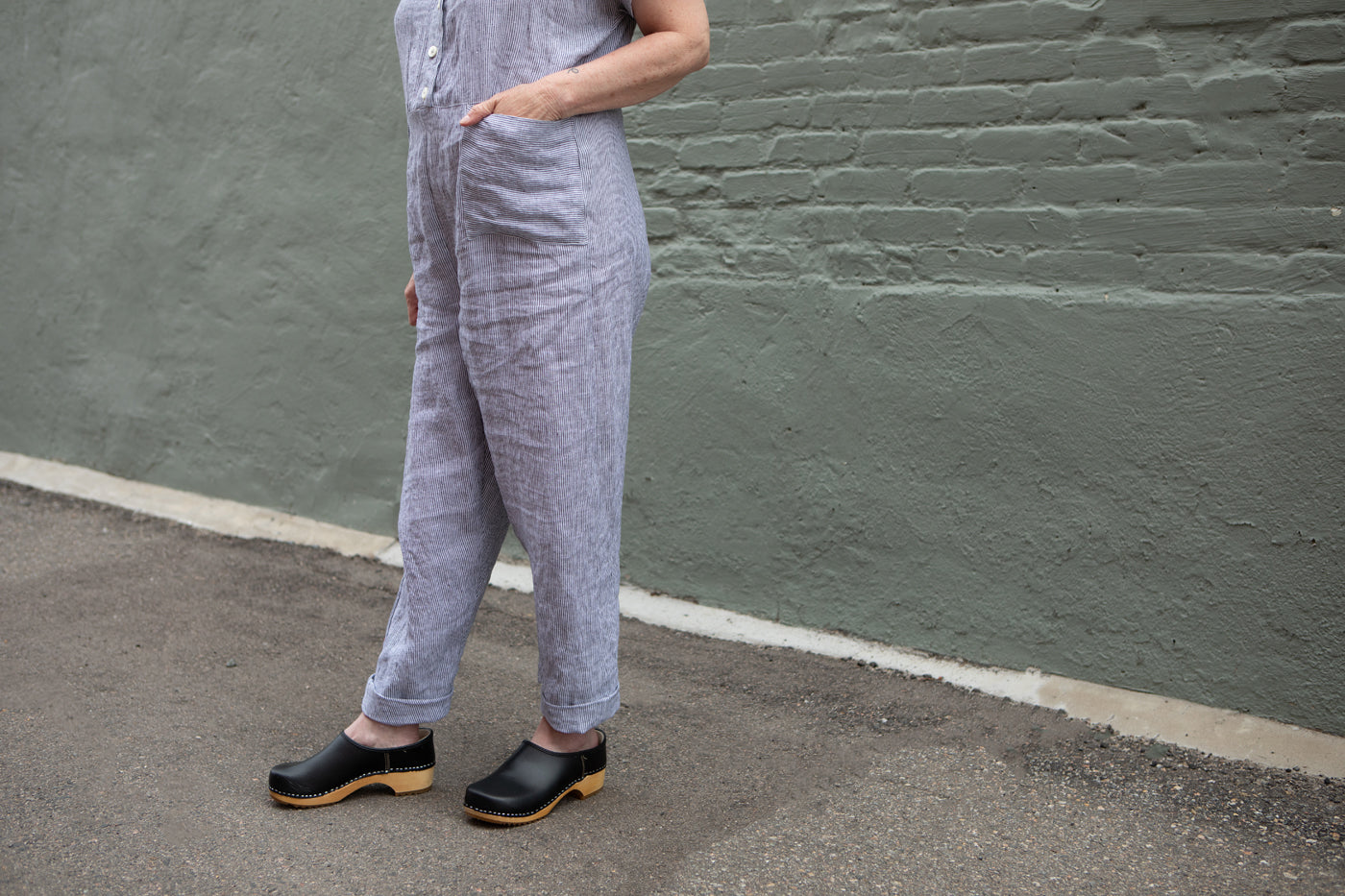 A close-up image of the bottom of Christina's linen jumpsuit. Her hand is in her pocket and she wears black clogs with wooden soles.