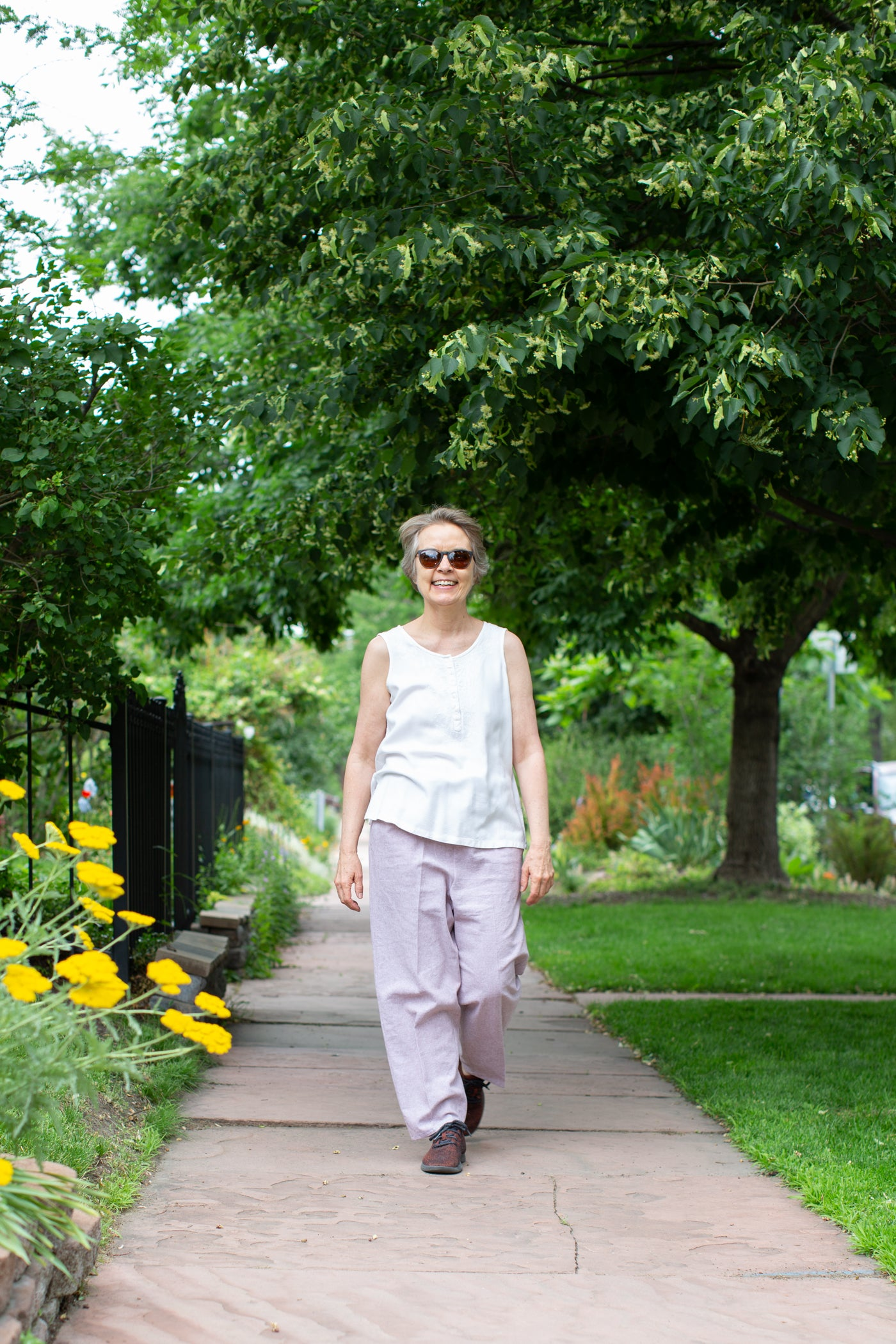 Women walking down the city sidewalk smiling, wearing sunglasses, white tank top and Mocha colored pants.