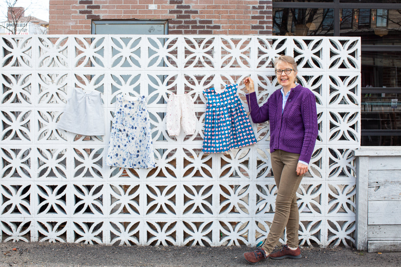 Alek standing in front of a white brick wall, holding a string holding 4 baby garments.  Left to right light blue romper, watercolor blue dress, off white bloomers and last a little strawberry pattern dress.