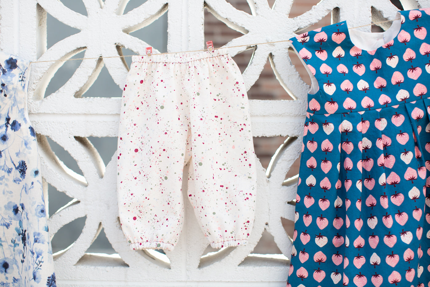 Little off white colorful splattered kids bloomers against a white brick wall.