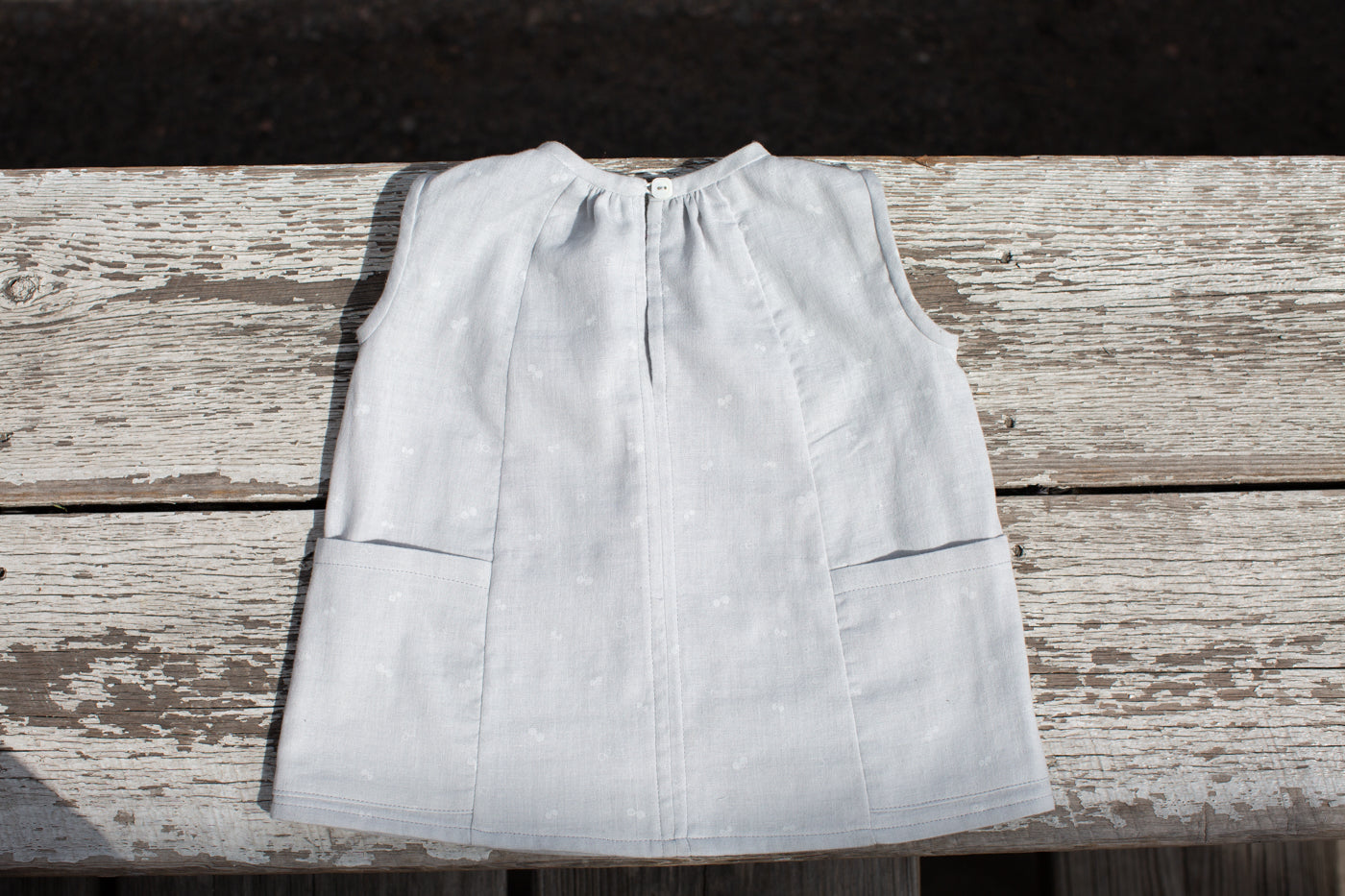 Pale blue little kids dress.  This is a lay flat with the dress on top of a rustic wooden ledge.