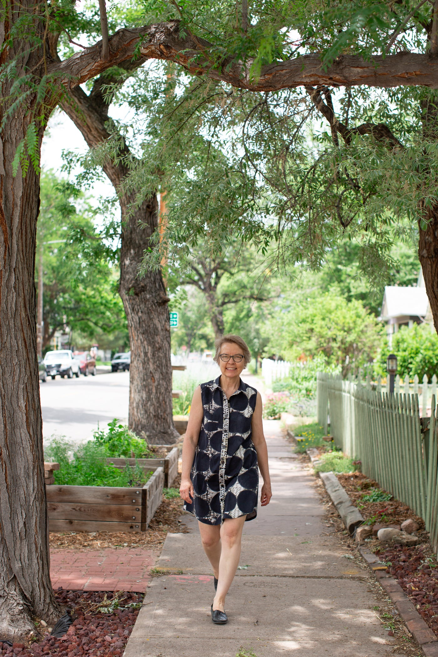 Aleks wearing a sundress walking down the city sidewalk with green trees surrounding her.