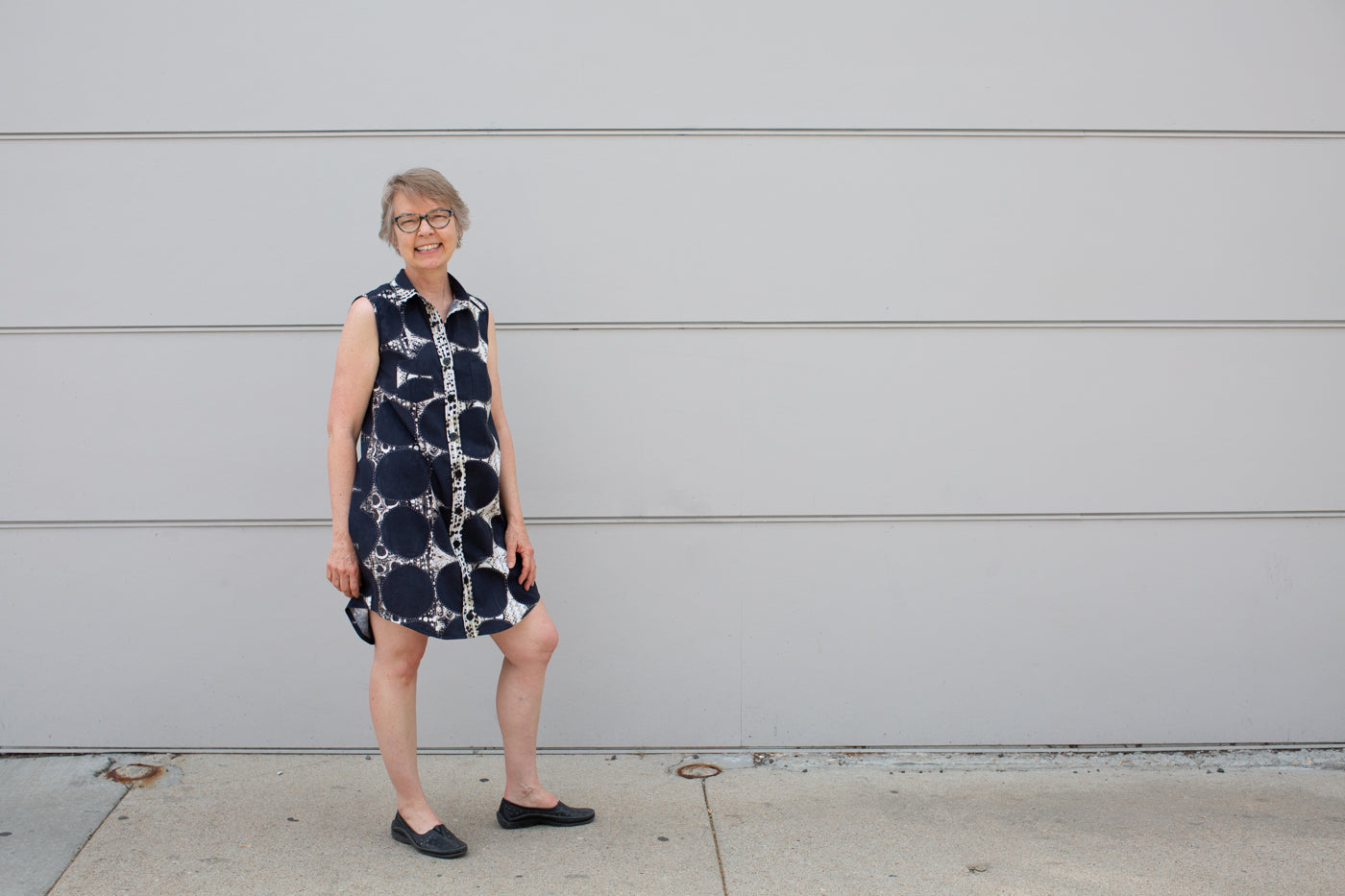 Aleks wearing a sun dress in front of a light grey wall, looking at the camera smiling.