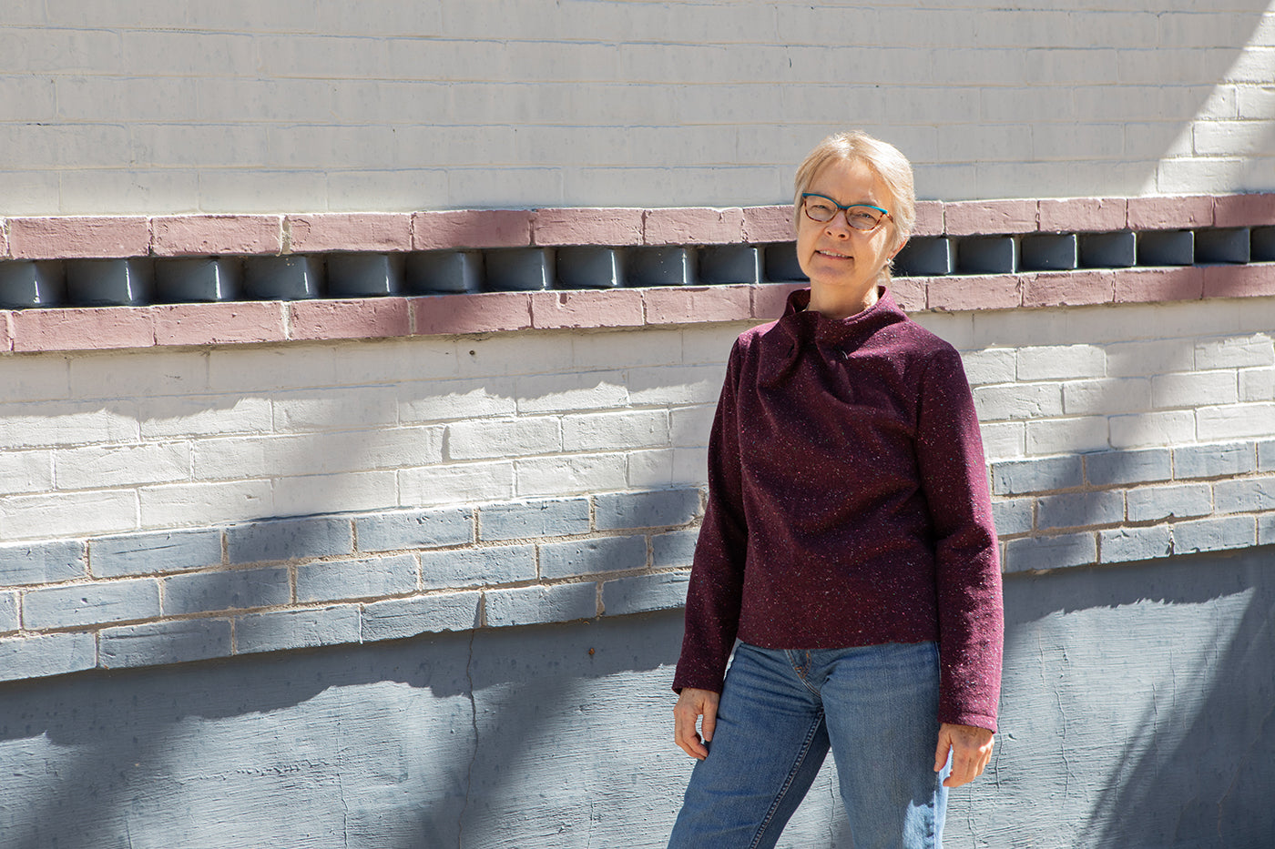 This is an image of a woman wearing a maroon flannel elastic neck shirt standing in front of a wall outside with diagonal shadows.