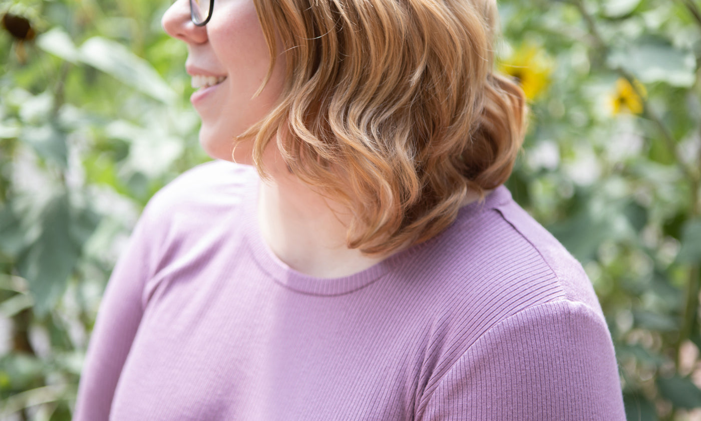 This is an image of a woman wearing a pinkish purple shirt standing in front of sunflowers outside.