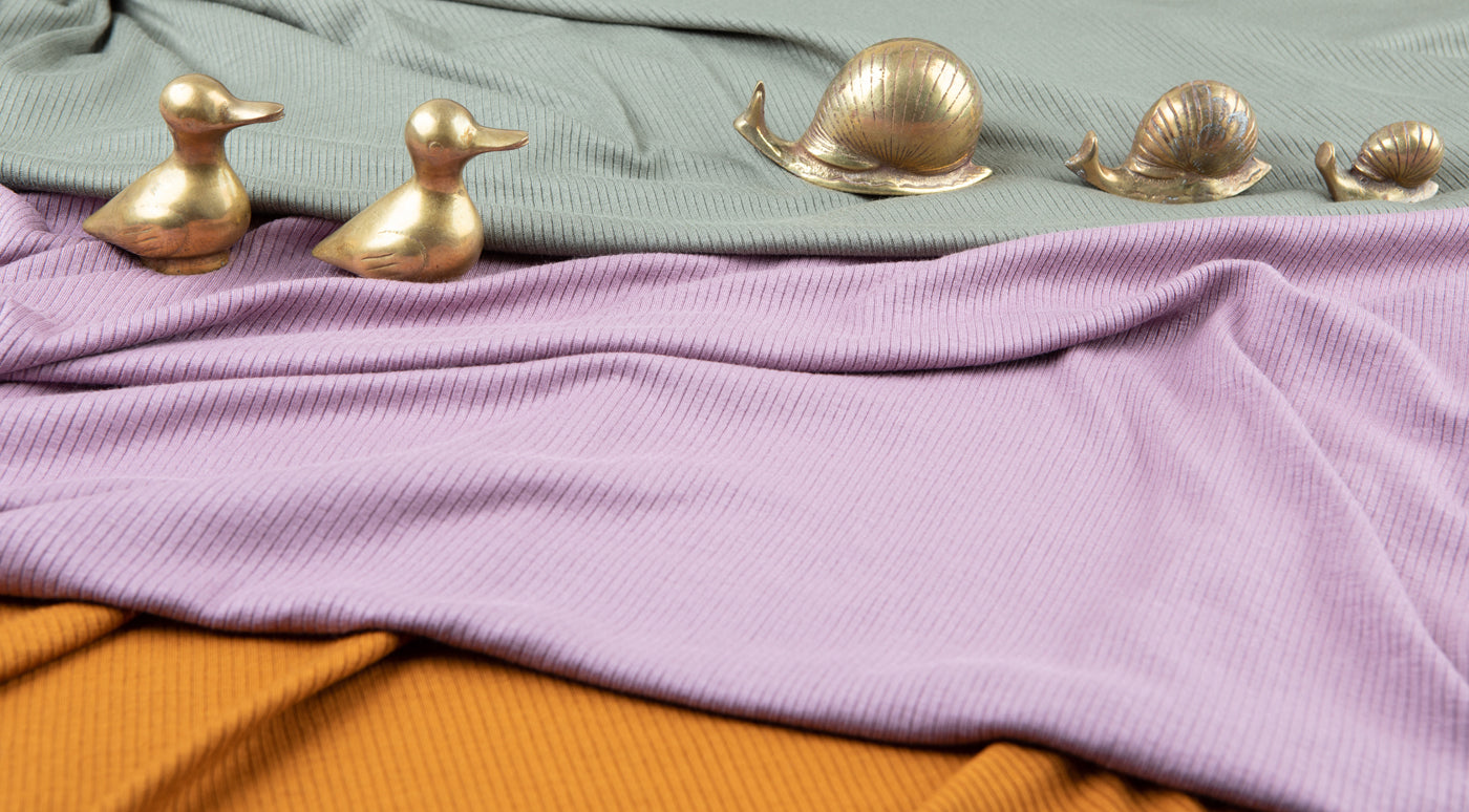 This is an image of several fabrics with brass animal figurines on top of them.