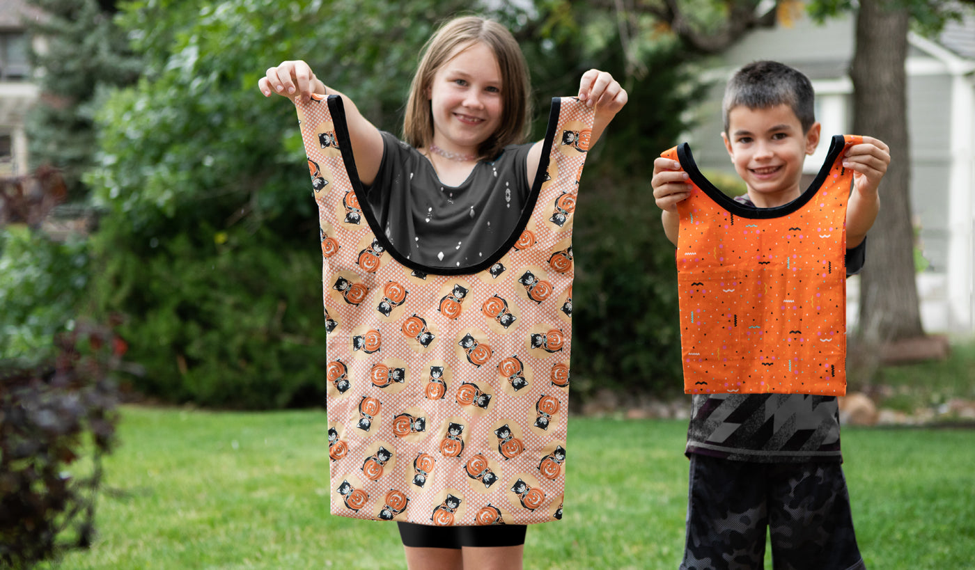 This is an image of a boy and girl holding up Halloween bags while standing outside.