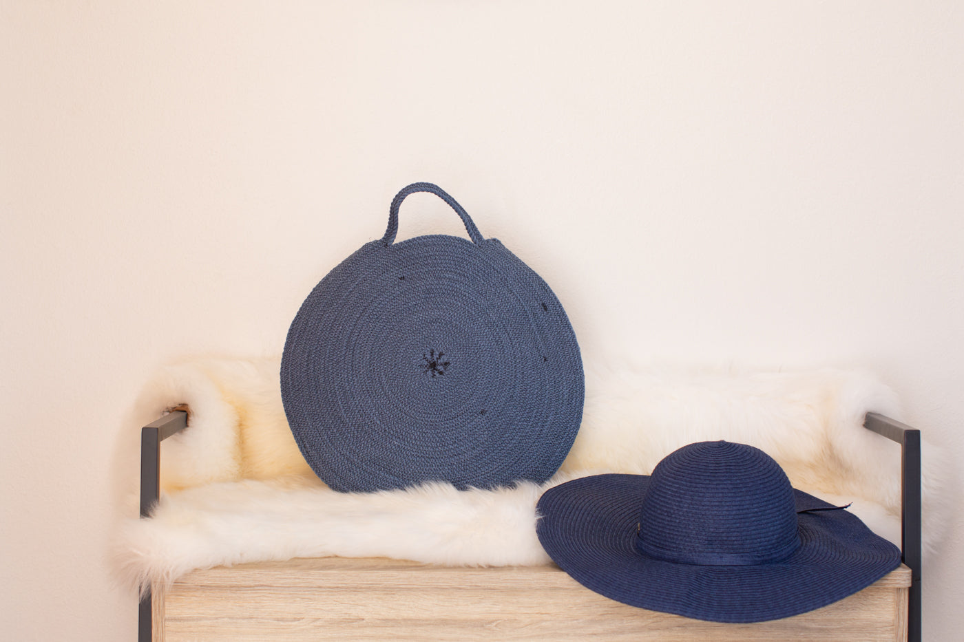 Navy blue rope bowl and navy sun hat sitting on a birch bench with black iron sides.  One top of the bench is a sheepskin fur with the rope bowl and hat sitting on top.