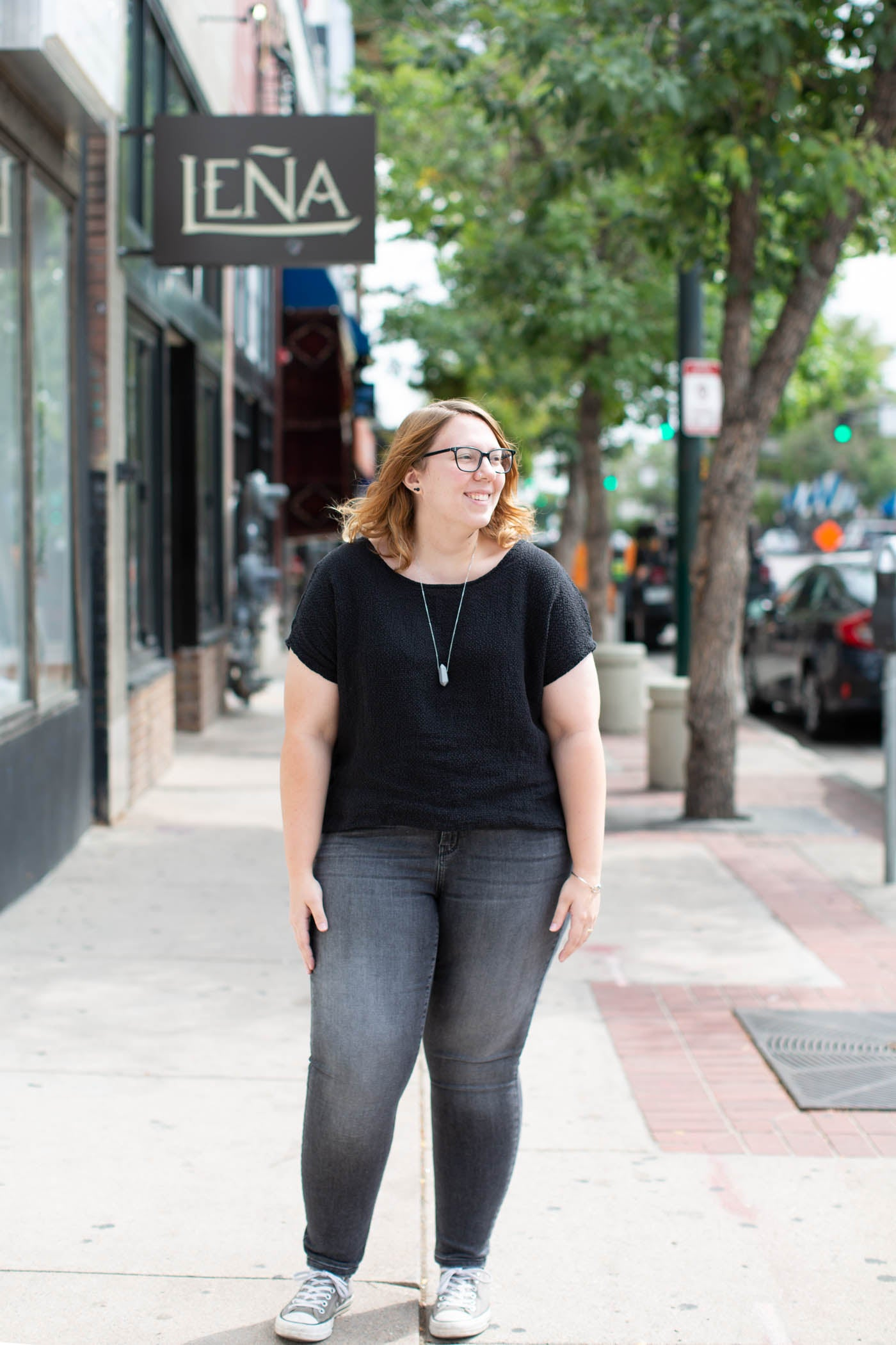 Women standing on a city sidewalk wearing a black top and grey jeans. Women has her hands down to her sides and looking towards the city street and smiling.