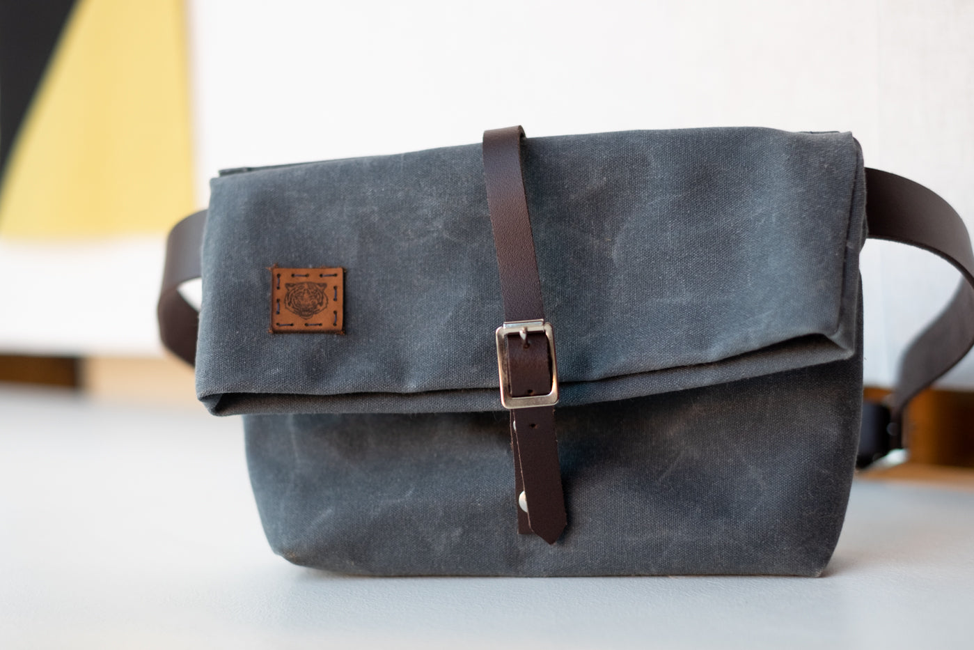 Slate waxed canvas bag with dark leather sitting upright agains a white background.