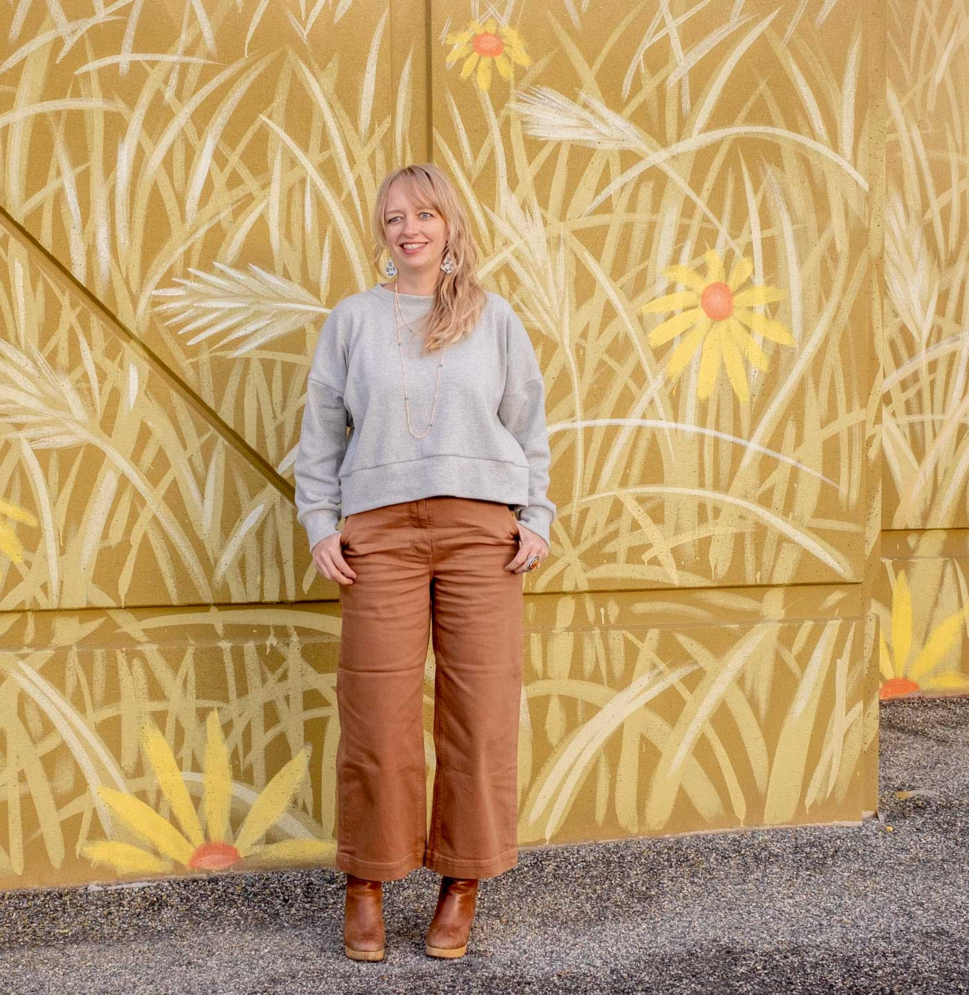 Amber wearing the Hosta sweatshirt—a slightly cropped, long sleeve, crew neck top—brown wide leg pants, and clog boots.