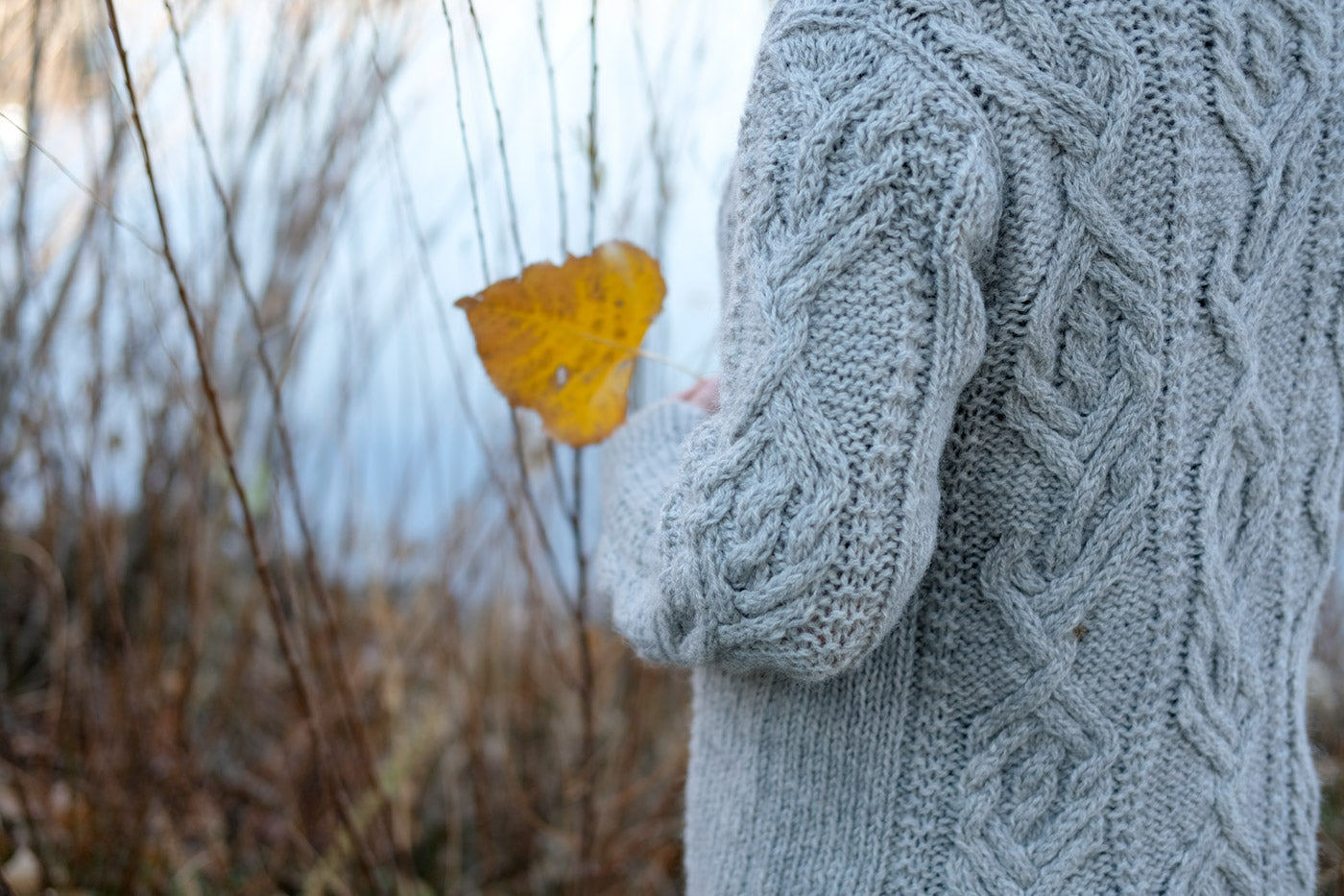 The elbow and shoulder of Amber's Junegrass Sweater while she holds a leaf