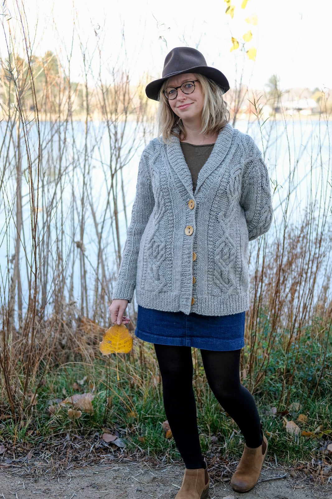 Amber by the lake holding a leaf in her Cabled Junegrass Sweater
